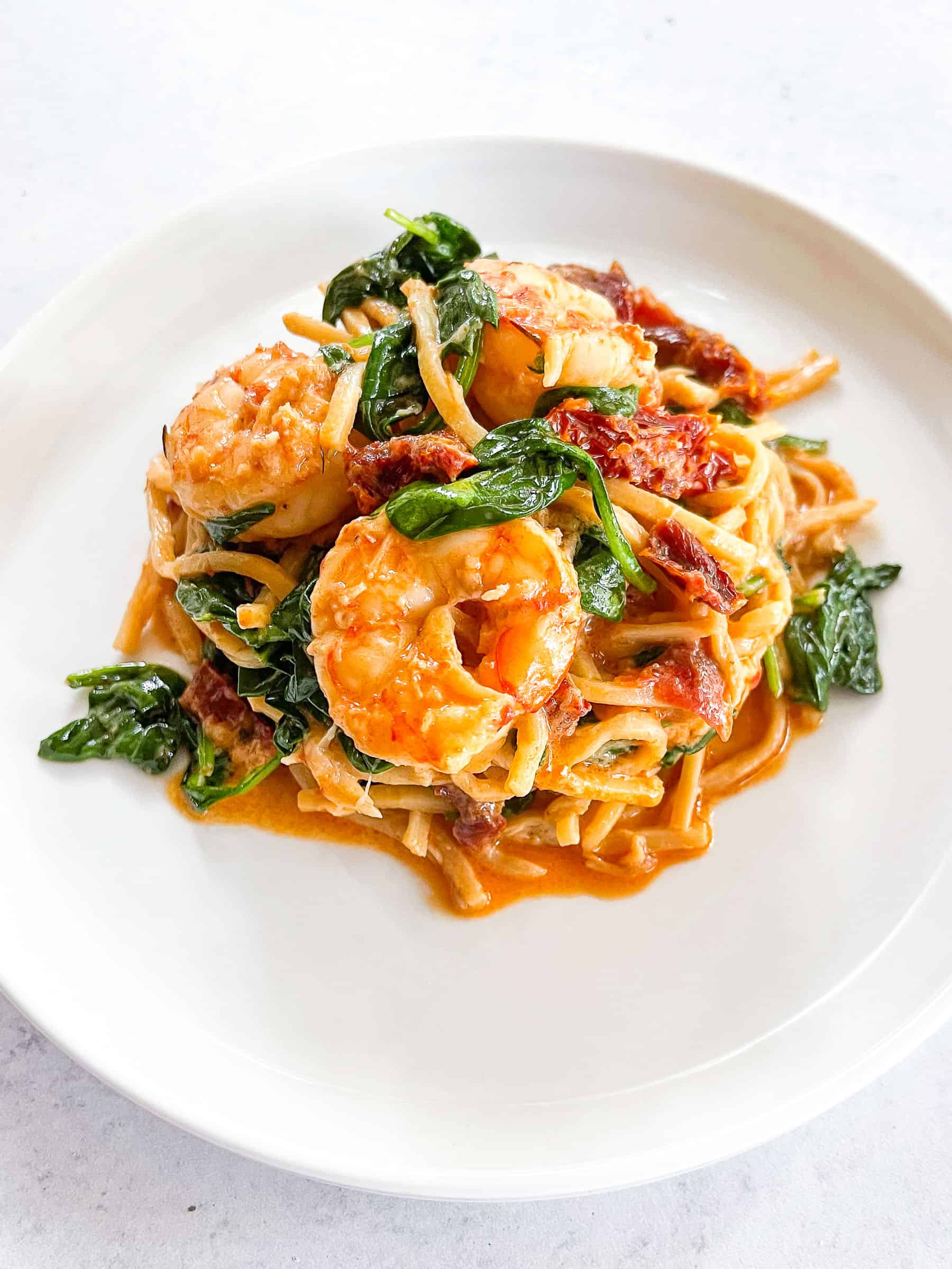 keto creamy tuscan shrimp pasta on a white plate with a white background