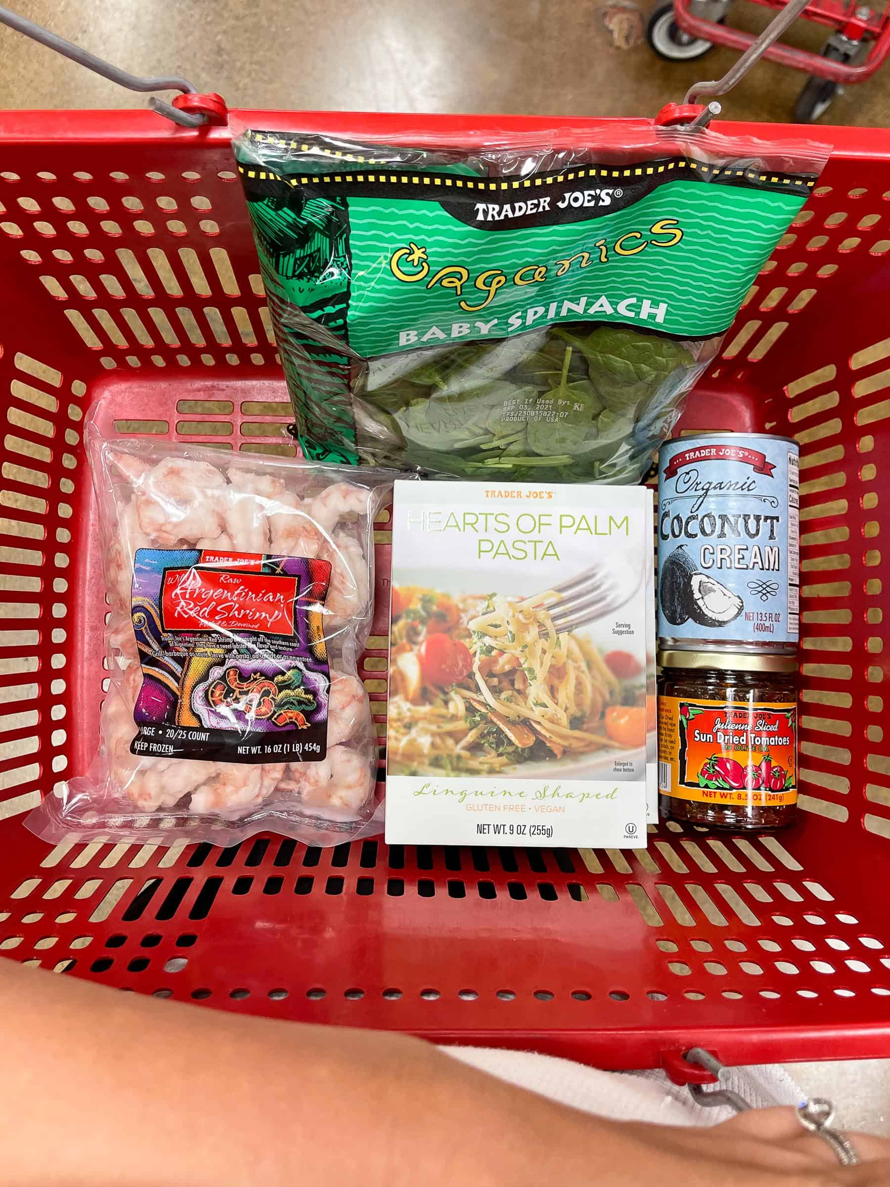 ingredients for keto creamy tuscan shrimp pasta in a red trader joe's basket