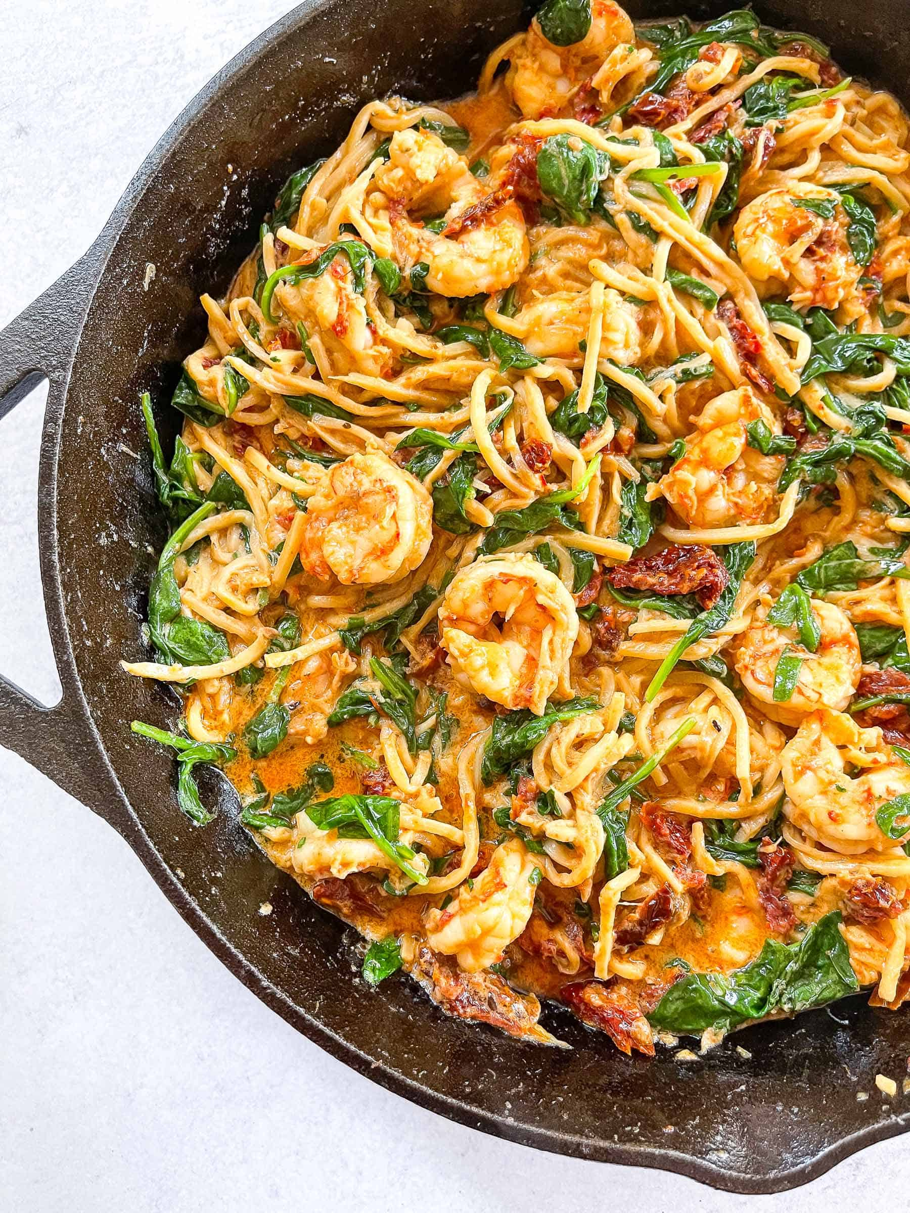 keto creamy tuscan shrimp pasta in a cast iron skillet with a white background