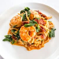 keto creamy tuscan shrimp pasta topped with basil on a white plate with a white background