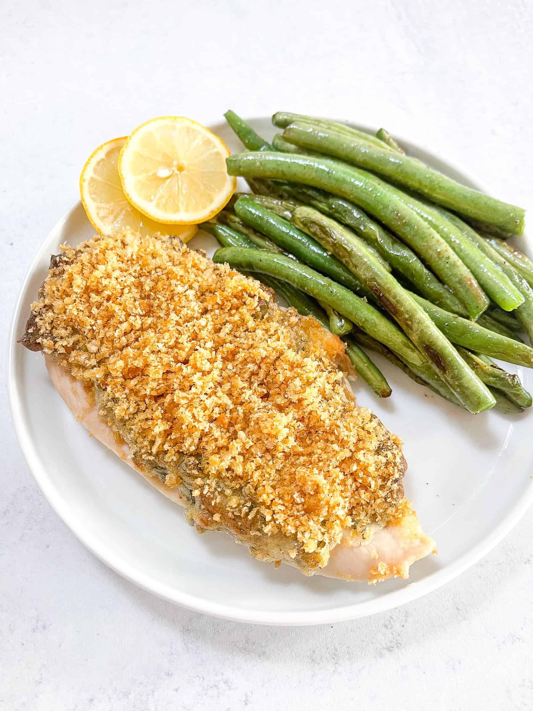 keto crispy ranch chicken with green beans and lemon garnish on a white plate with a white background