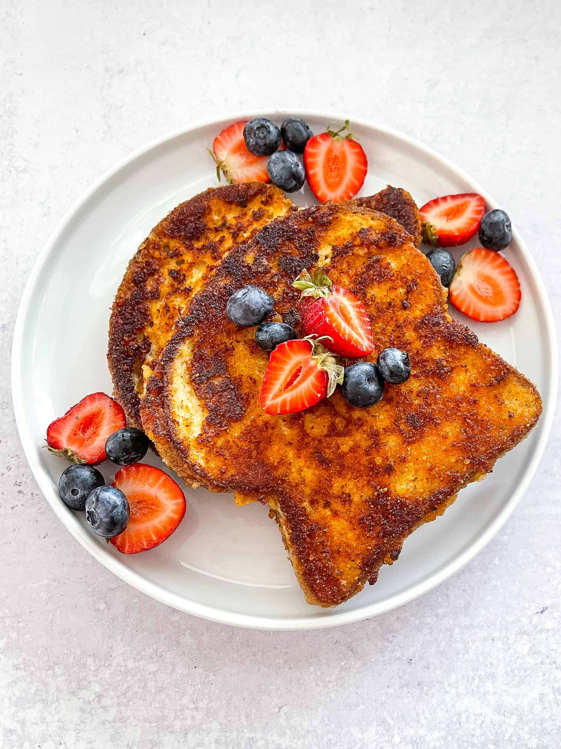 keto crusted french toast topped with syrup, blueberries, and strawberries on a white plate with a white background