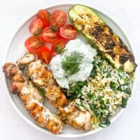 keto grilled chicken kabobs on a white plate with veggies and tzatziki sauce with a white background