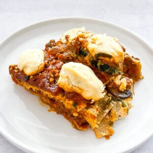 dairy free lasagna topped with dairy free ricotta cheese on a white plate with a white background