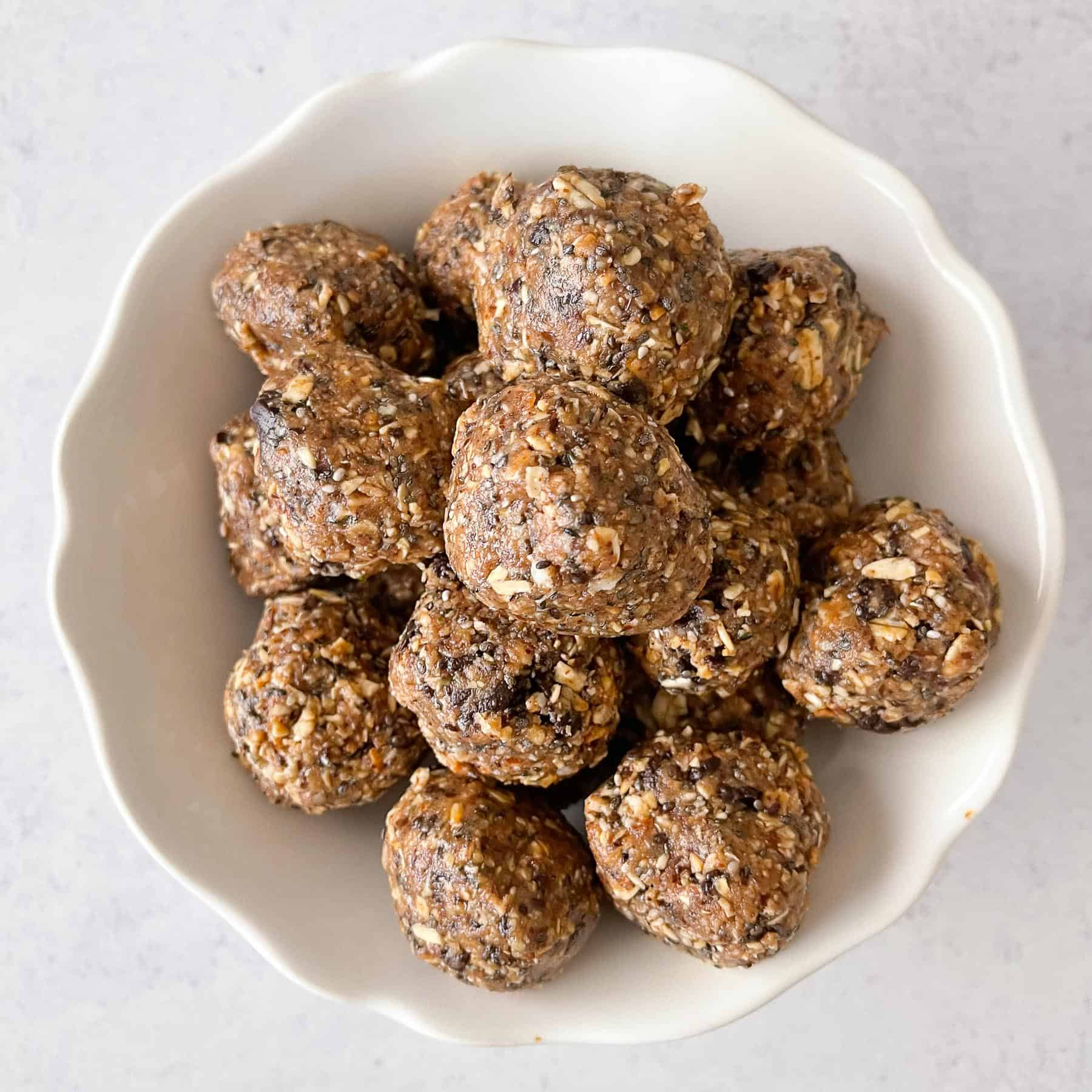 energy bites aka no bake cookie balls in a white bowl with a white background