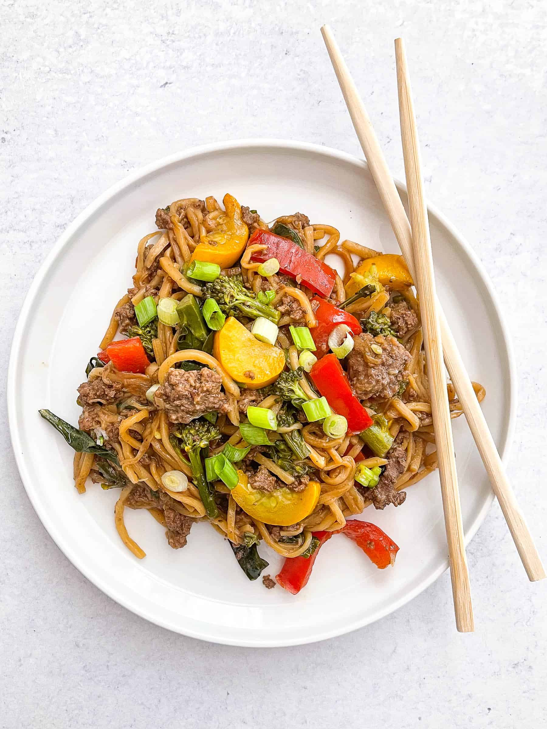 keto beef and vegetable noodle stir fry on a white plate with two chopsticks and a white background