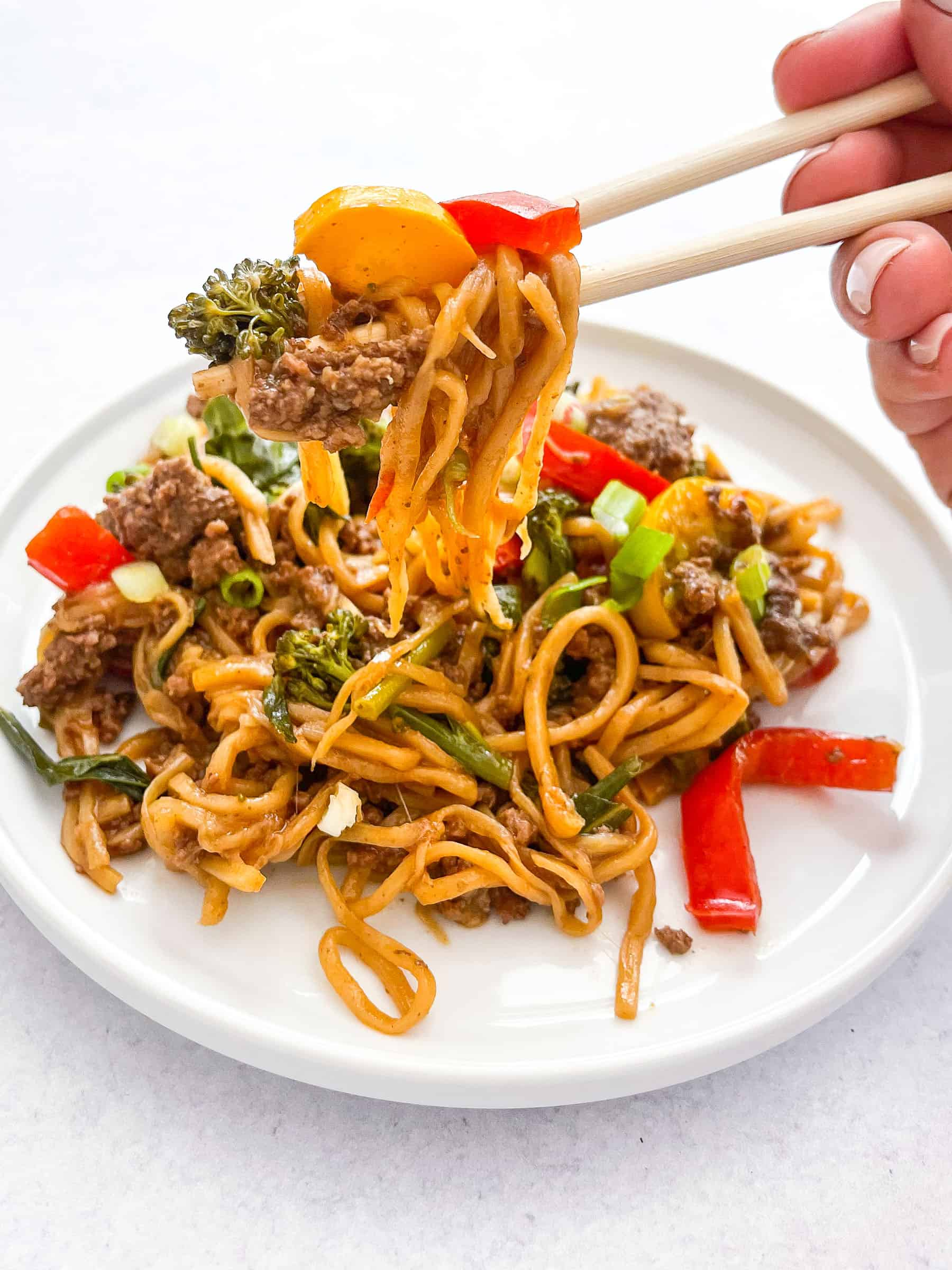 keto beef and vegetable noodle stir fry on a white plate with two chopsticks holding the stir fry with a white background