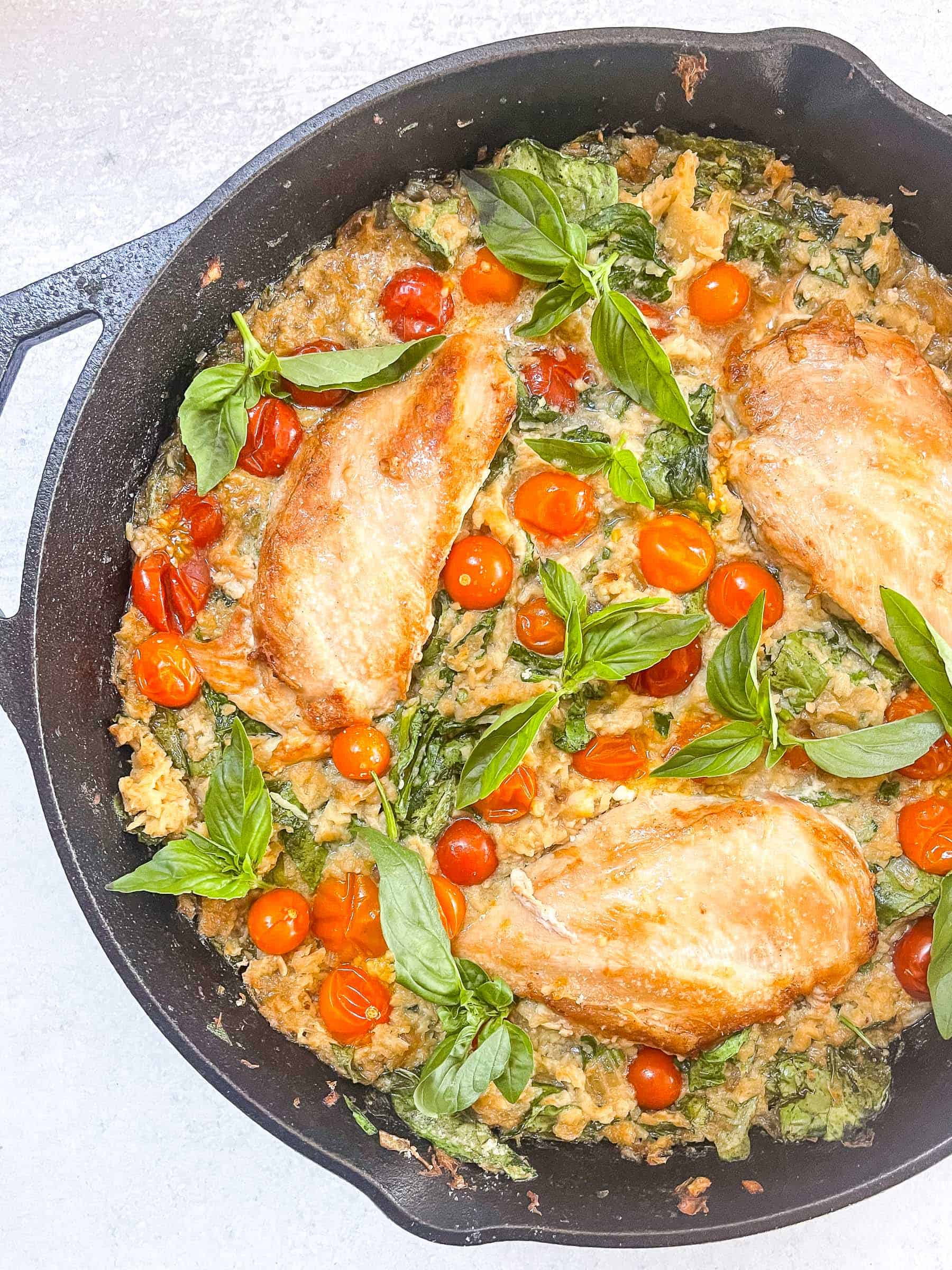 keto creamy chicken and tomato casserole in a black cast iron skillet with a white background