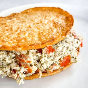 keto pesto chicken salad on cauliflower thins on a white plate with a white background