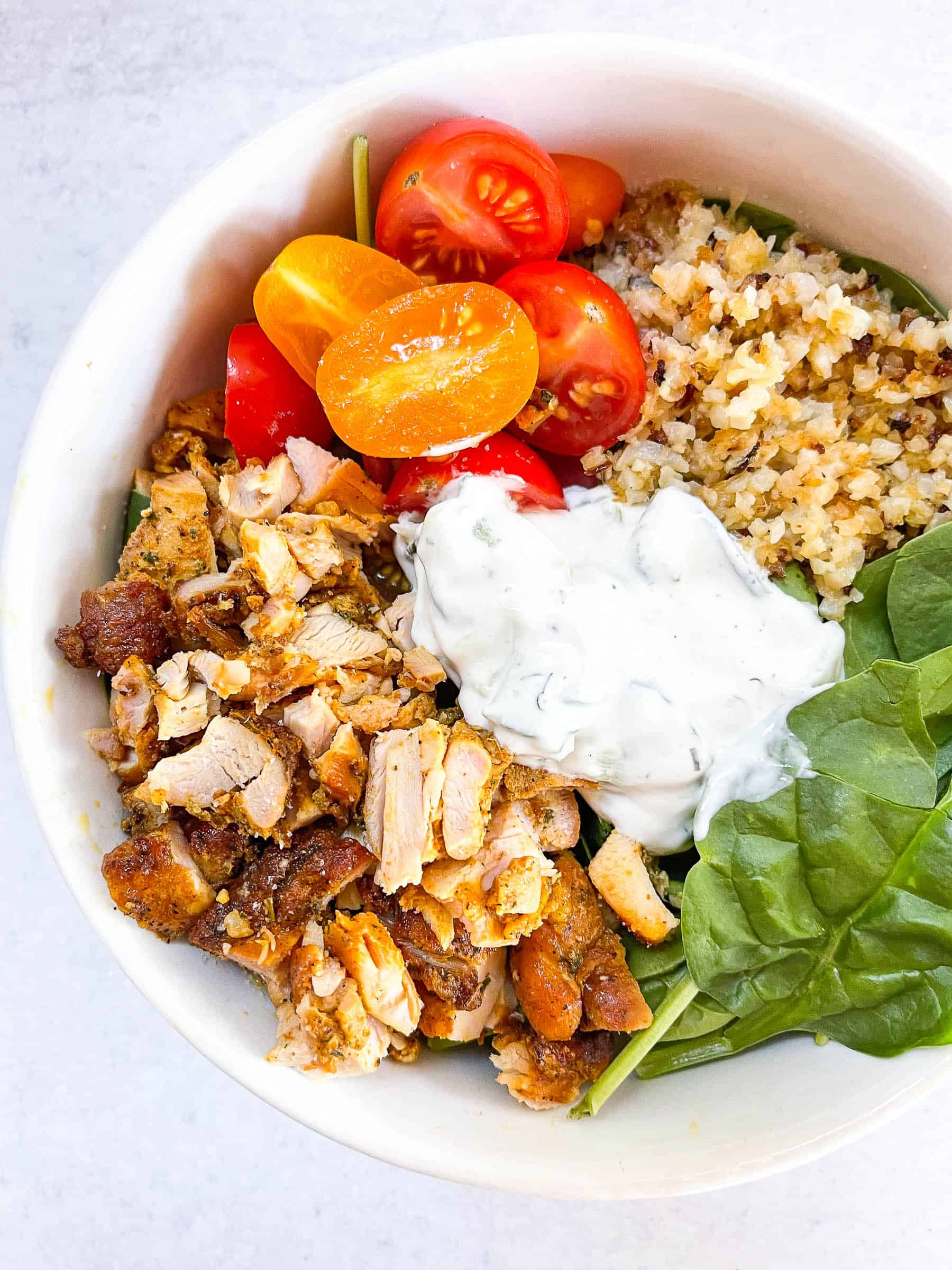 keto sheet pan chicken shawarma bowls in a white bowl with a white background