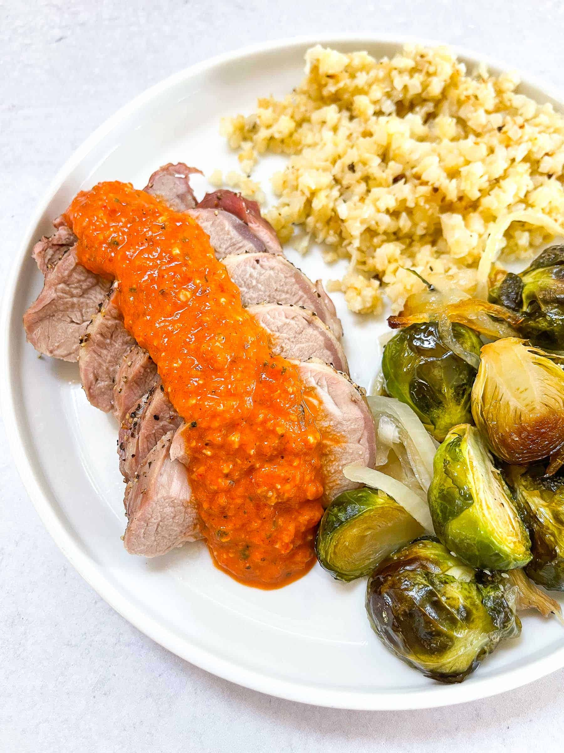 keto sheet pan pork tenderloin with romesco on a white plate with Brussel sprouts and cauliflower rice with a white background