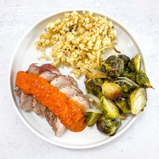 keto sheet pan pork tenderloin with romesco on a white plate with Brussel sprouts and hearts of palm rice with a white background