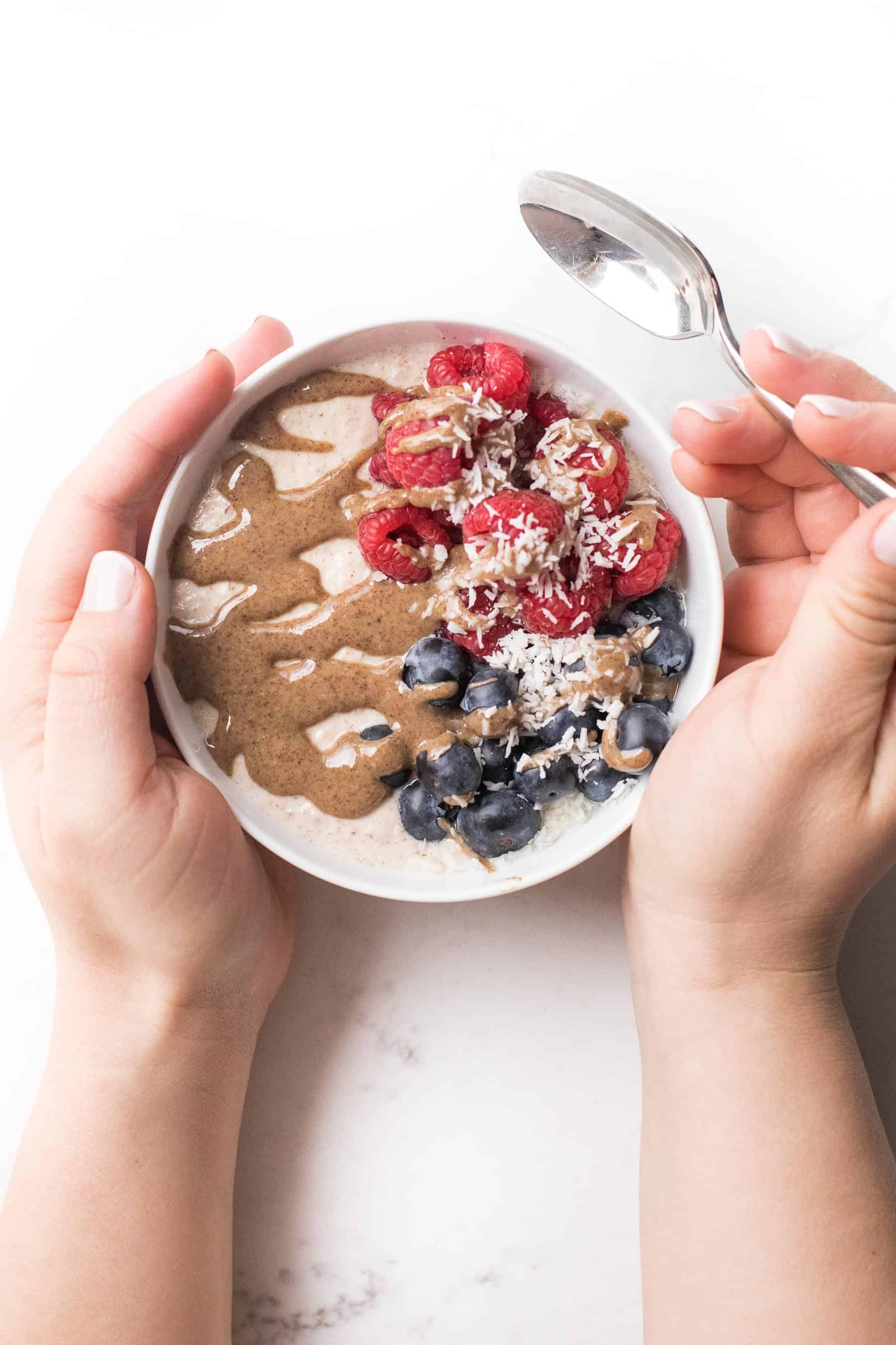 2 hands holding a bowl with breakfast porridge, berries and nut butter