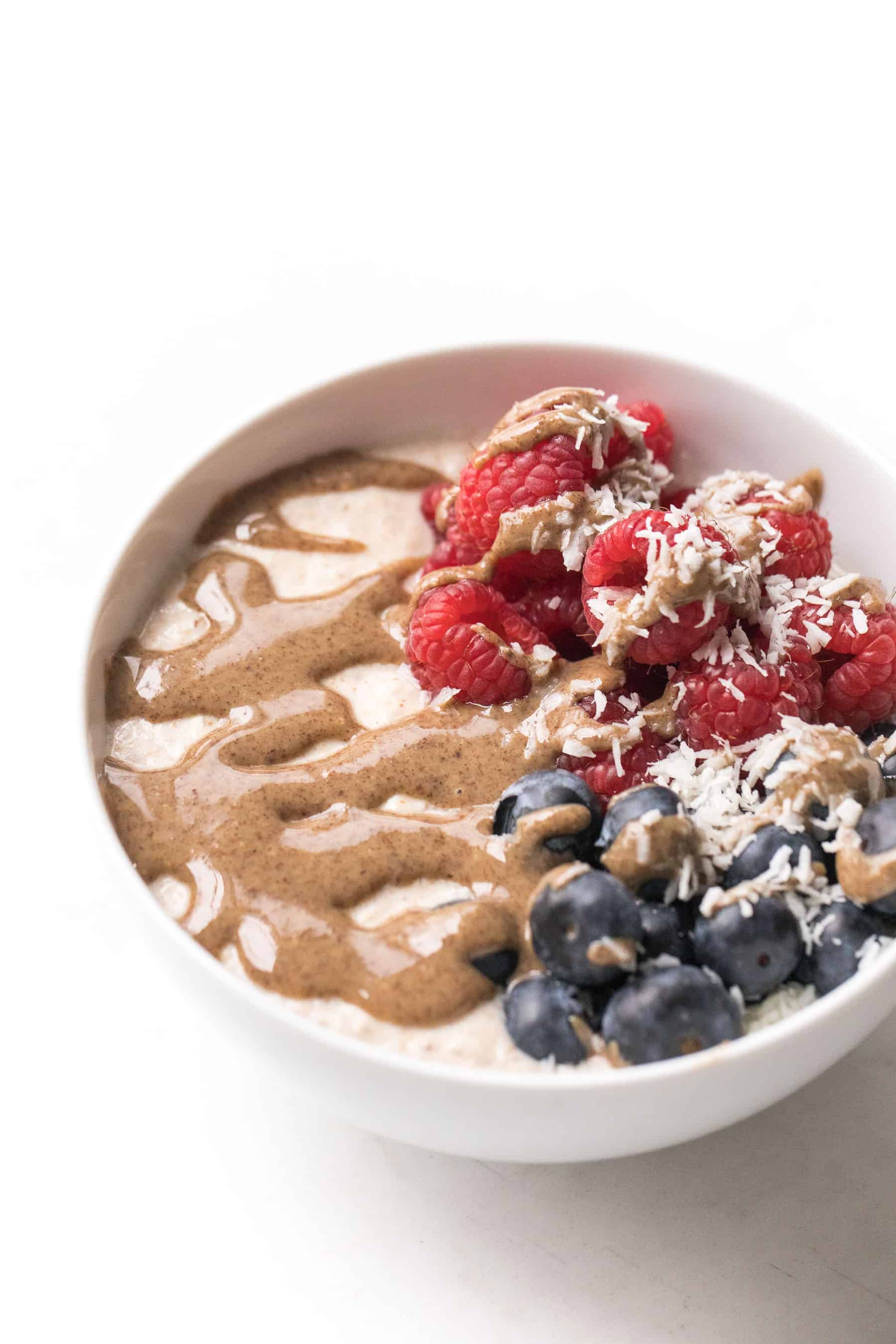 white bowl with breakfast porridge, berries and nut butter