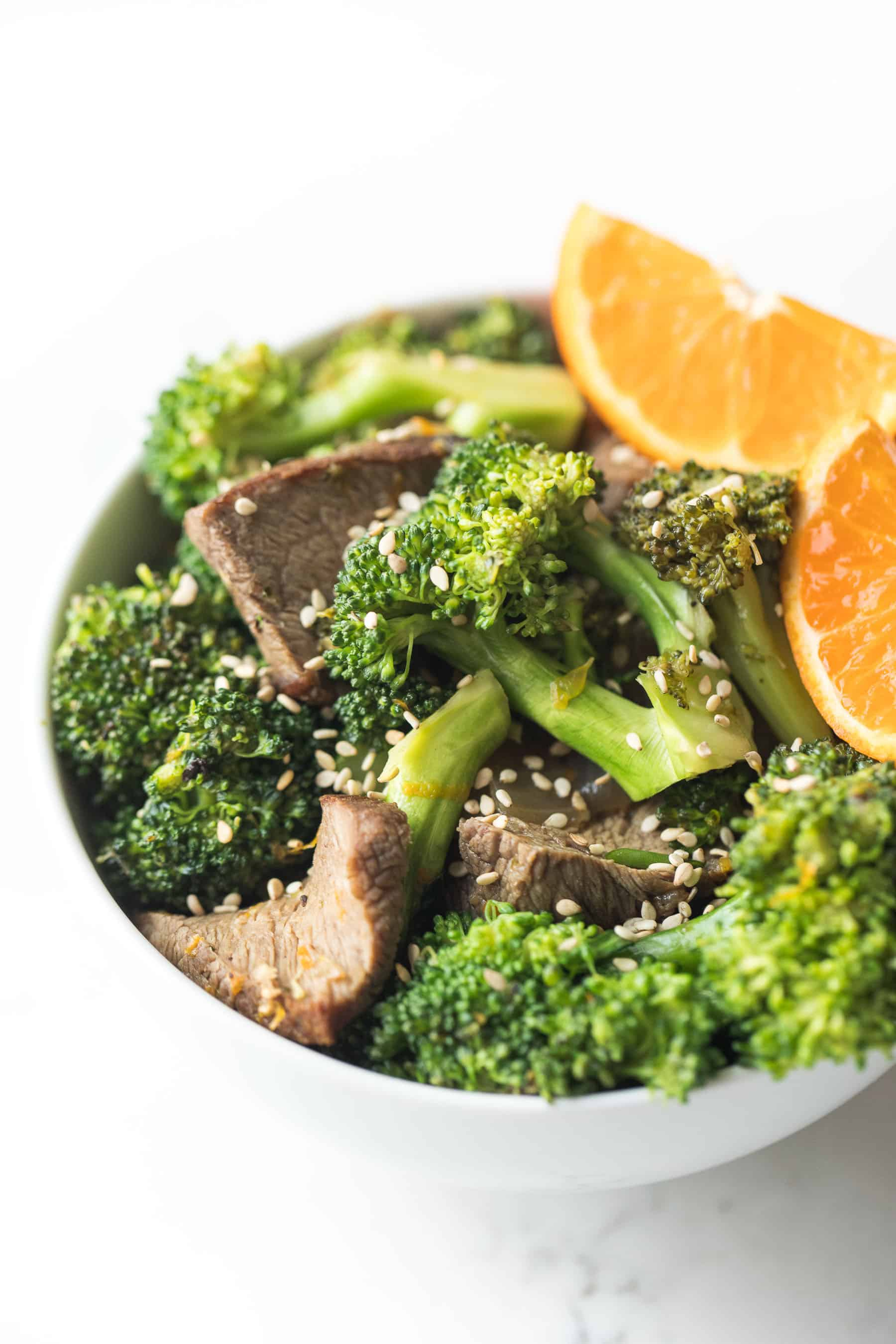 orange broccoli beef in a white bowl