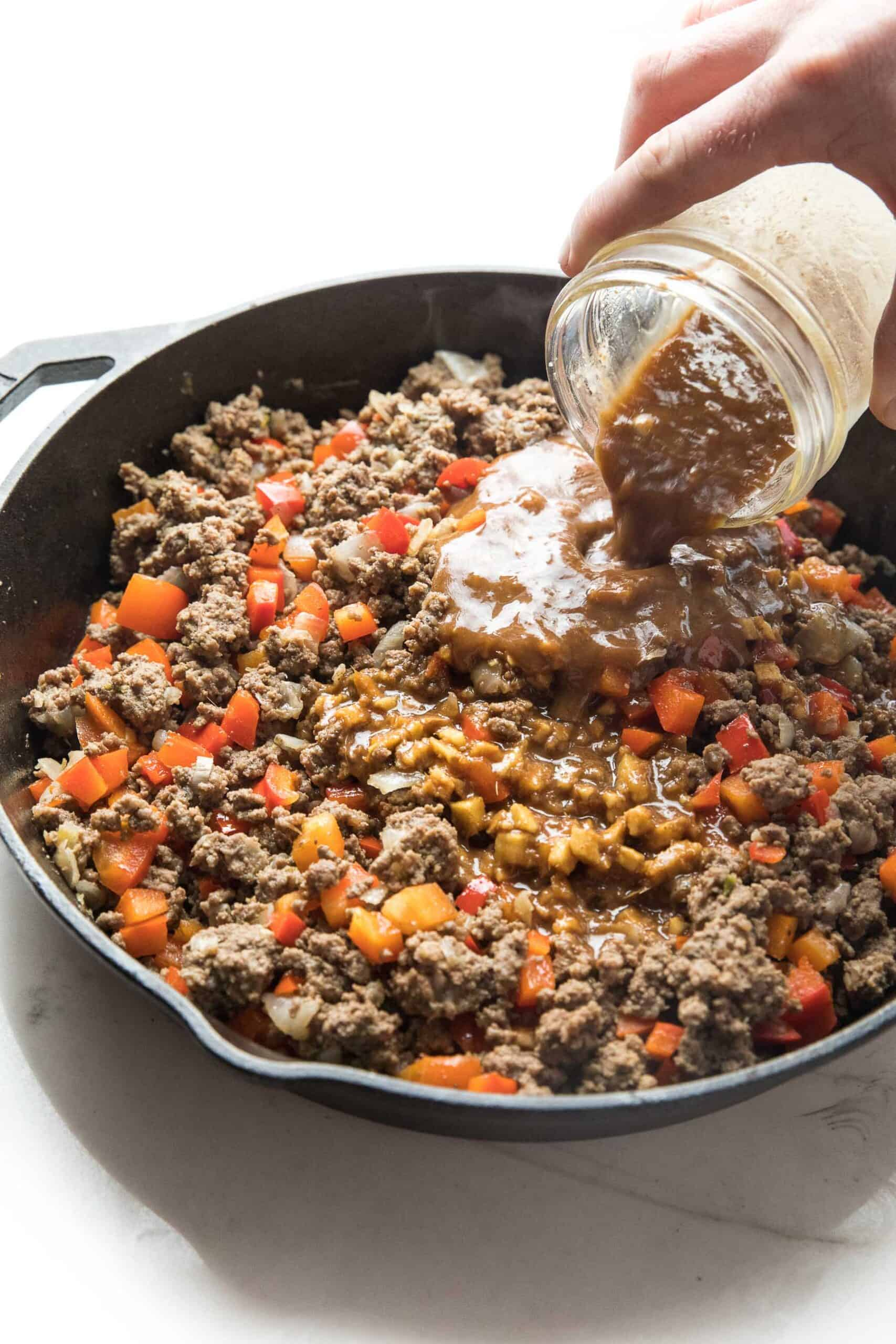 pouring sauce over ground beef and bell peppers in a cast iron skillet