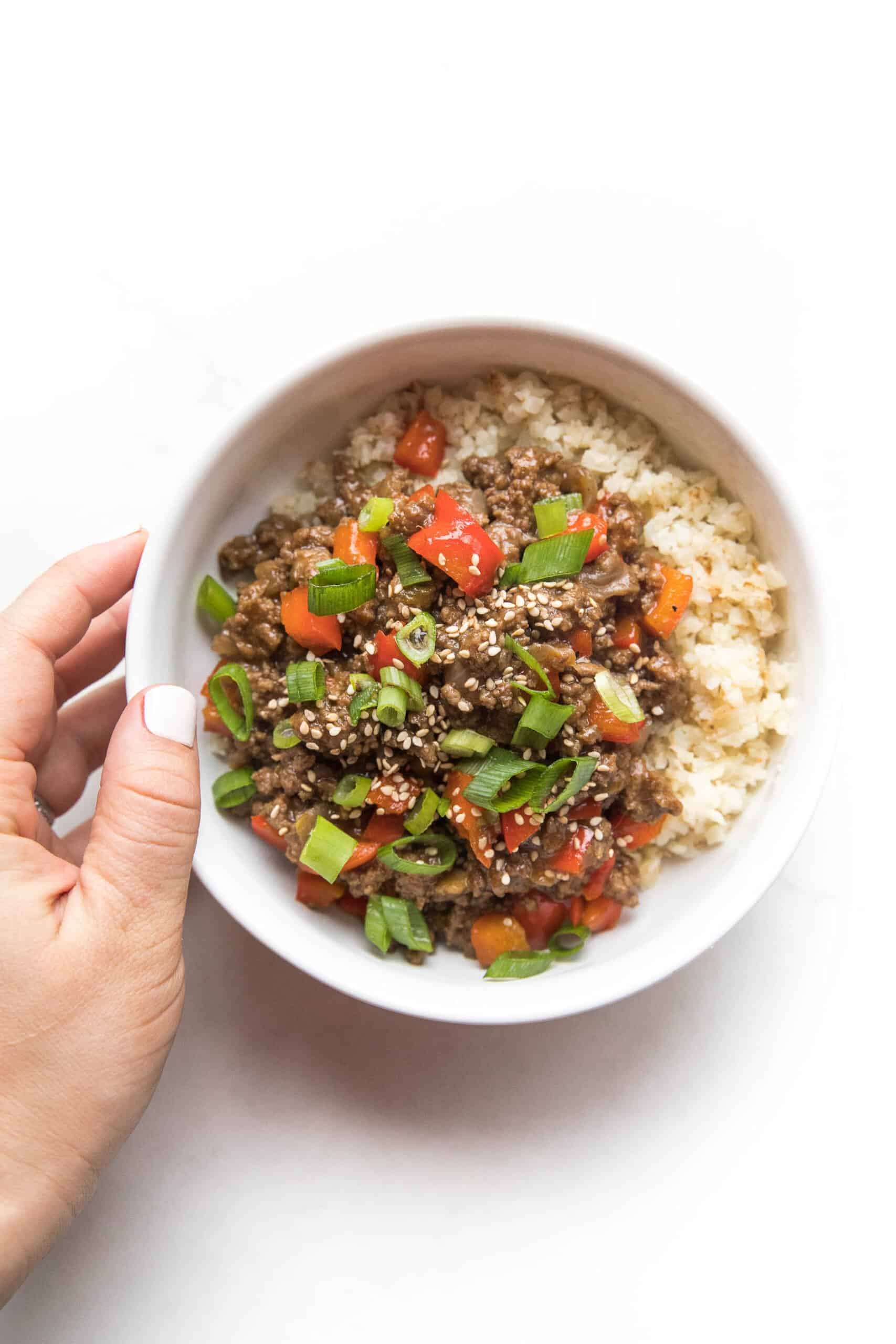 hand holding ground asian beef + bell peppers topped with green onions over cauliflower rice in a white bowl