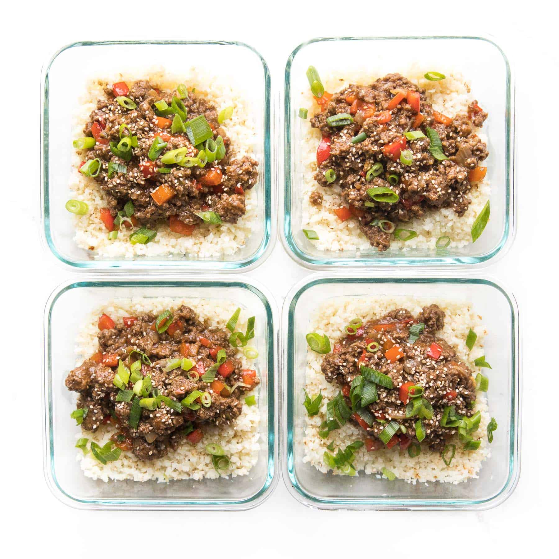 ground asian beef + bell peppers topped with green onions over cauliflower rice in a meal prep container