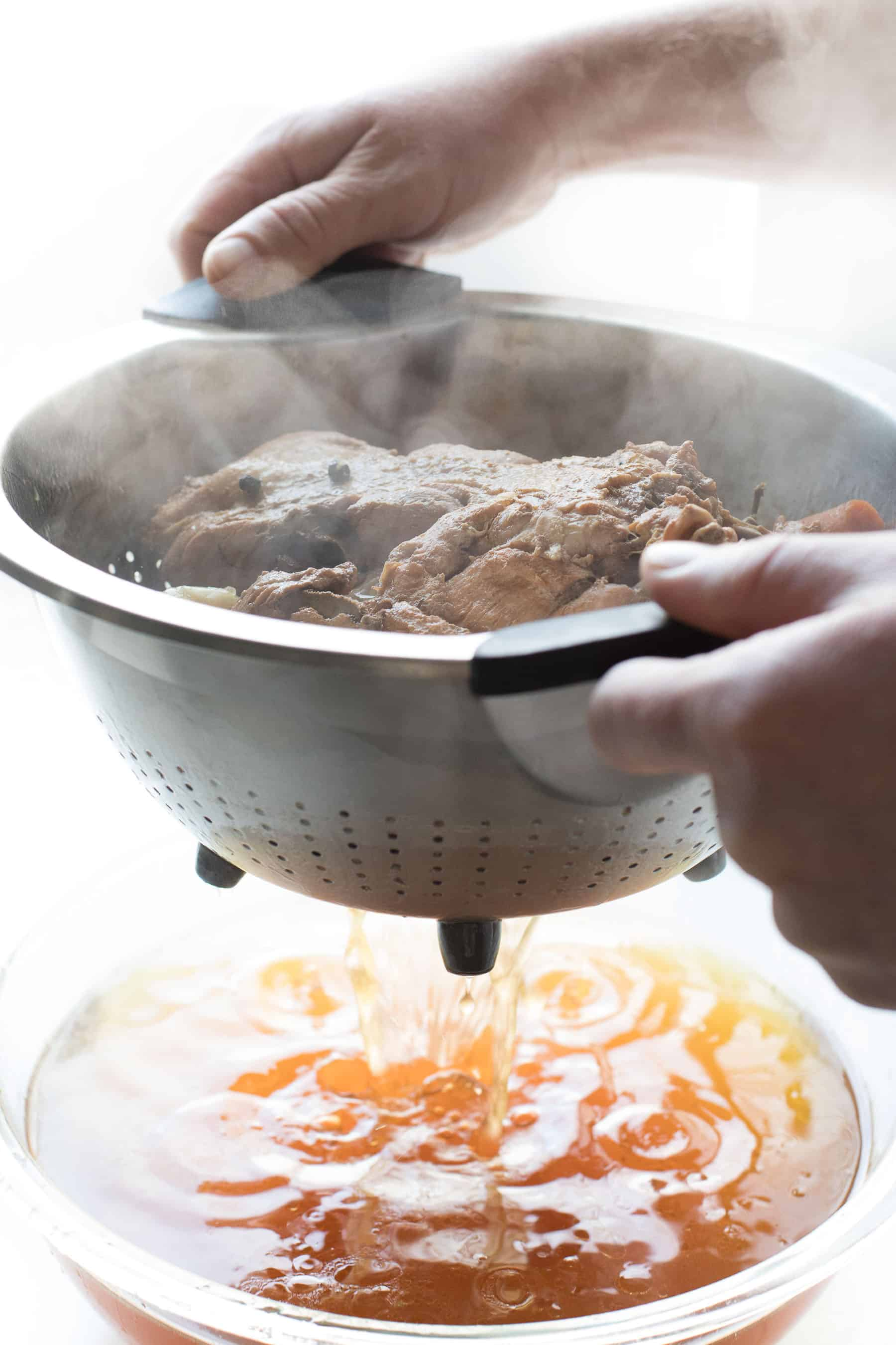 straining bone broth through a collander