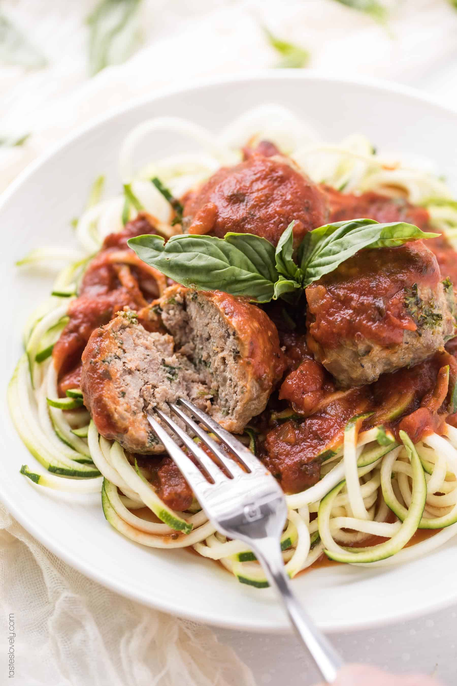 Easy Paleo & Whole30 Italian Meatballs Recipe - made with almond flour and served with marinara sauce over zoodles. The most delicious, moist, flavorful meatballs! Gluten free, grain free, dairy free, sugar free, clean eating, freezer friendly.