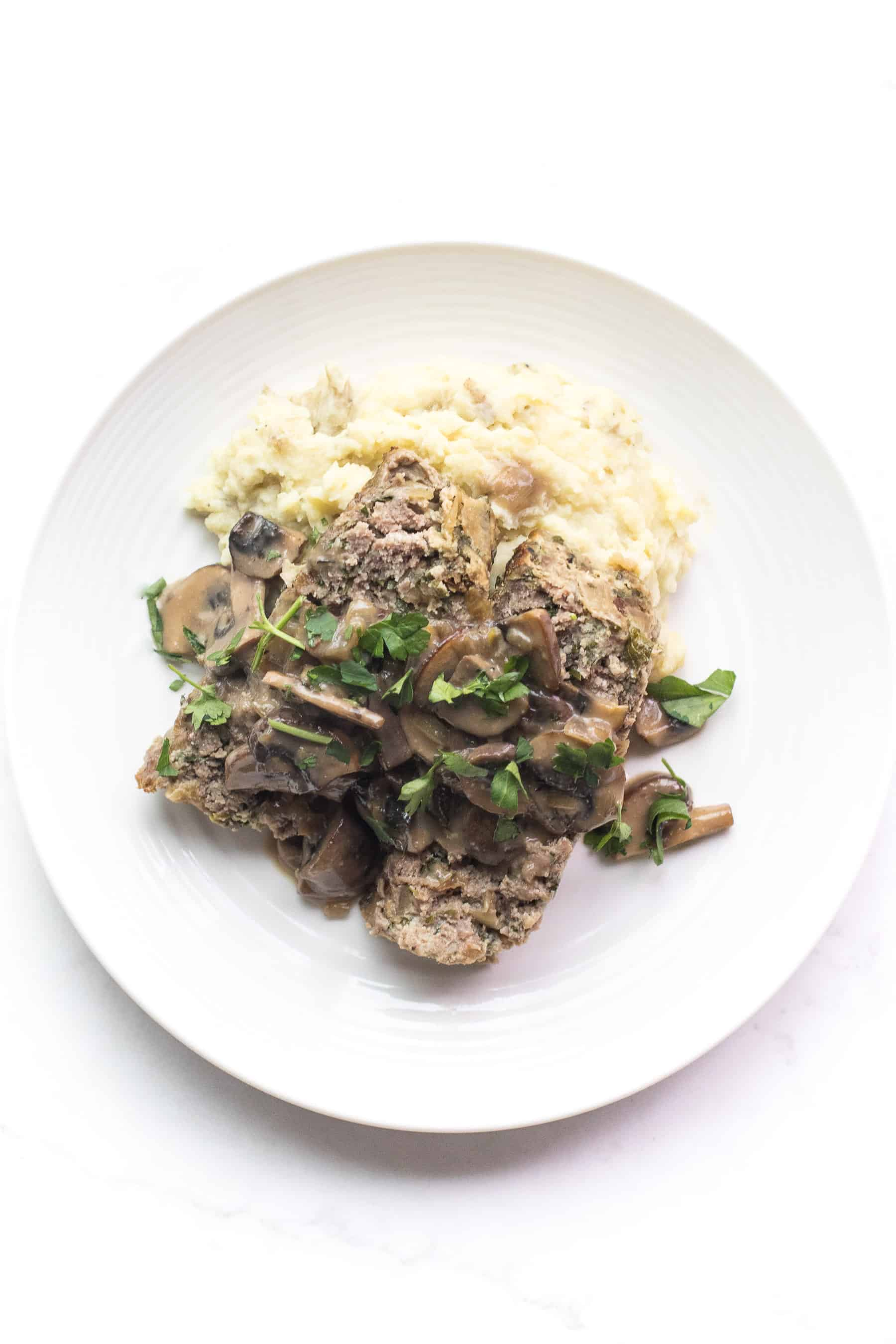 white plate with meatloaf and mushroom gravy over mashed potatoes