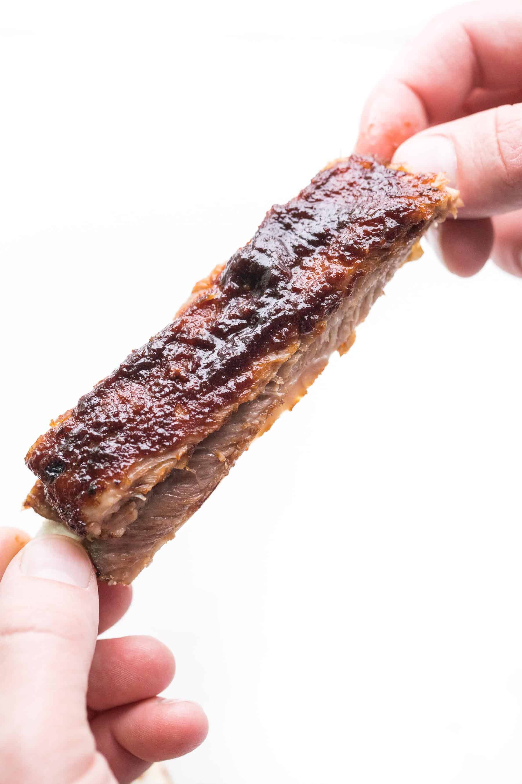 2 hands holding a bbq rib