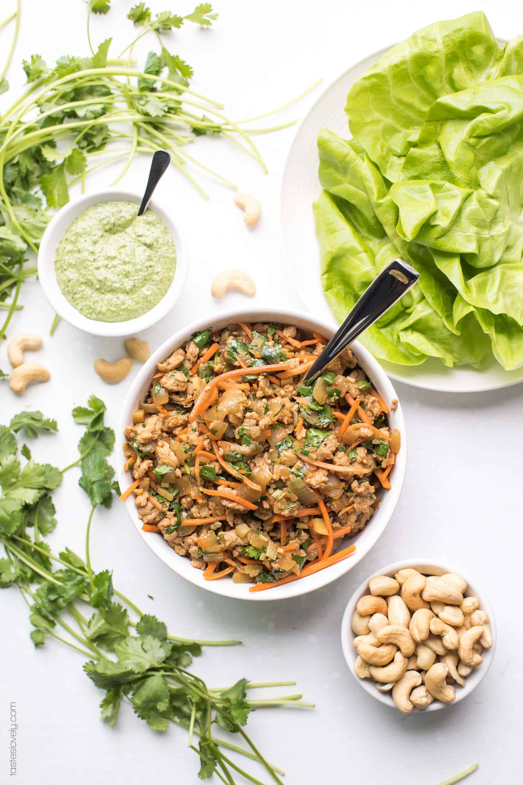 Paleo + Whole30 Thai Chicken Lettuce Wraps - a quick and healthy dinner recipe with ground chicken, sauteed onions, a thai sauce, cilantro and shredded carrots. Topped with a bright and fresh herby green dressing and cashews. #paleo #whole30 #glutenfree #grainfree #dairyfree #sugarfree #keto #cleaneating #realfood
