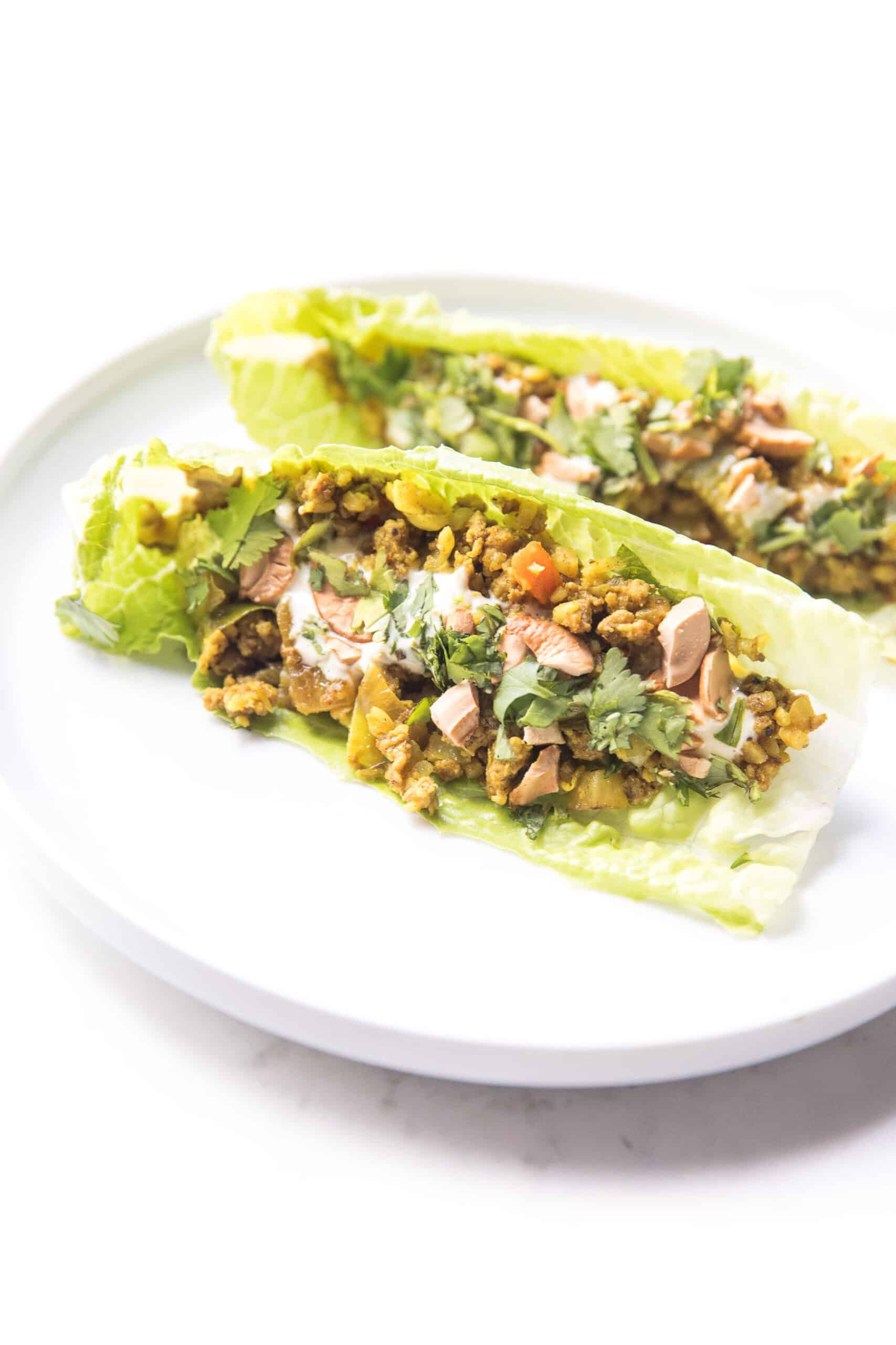 Curry lettuce wraps with cashews and cilantro on a white plate