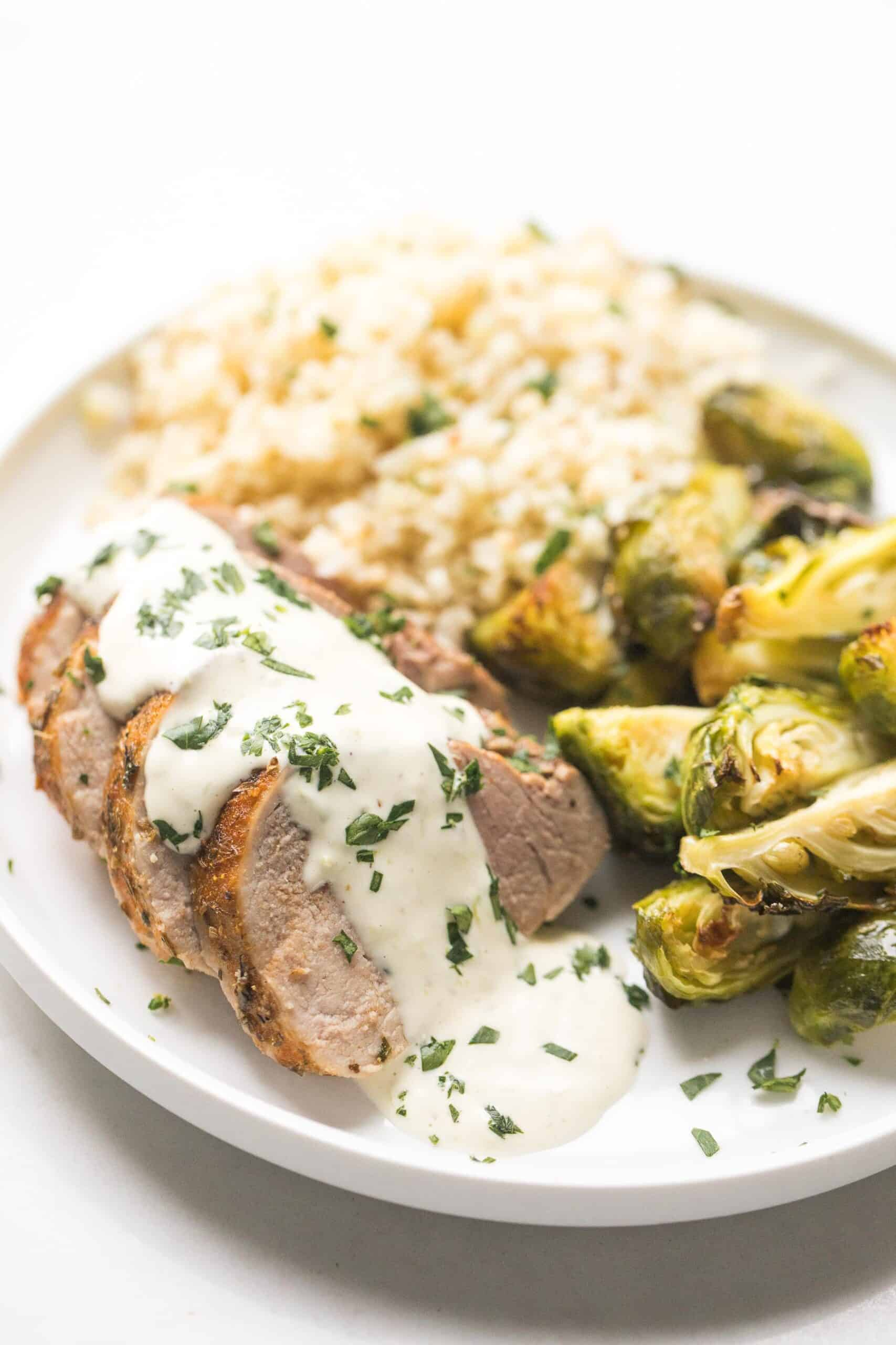 blackened pork tenderloin topped with white sauce lime garlic aioli with with brussels sprouts and cauliflower rice
