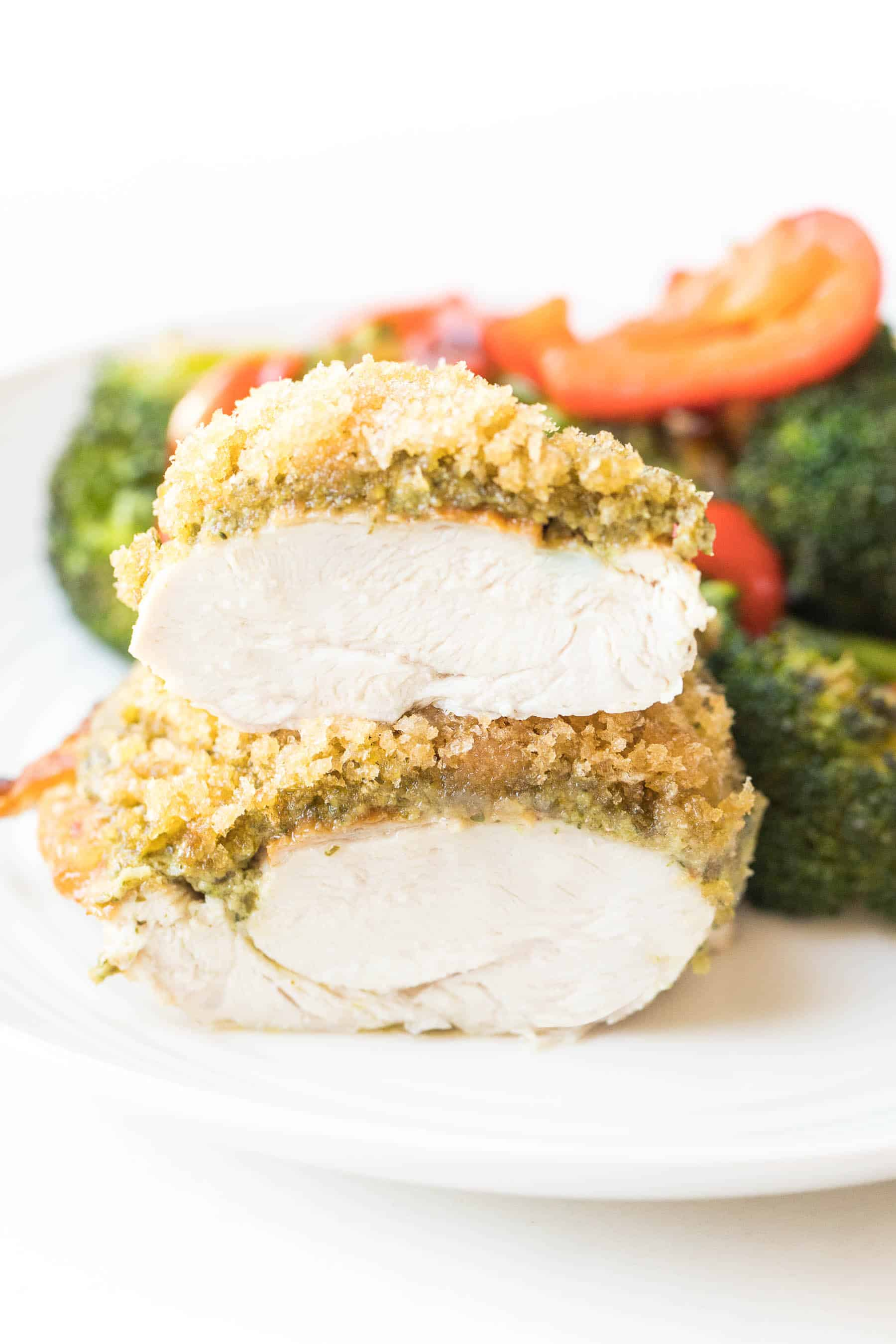 Crispy pesto chicken cut in half on a white plate