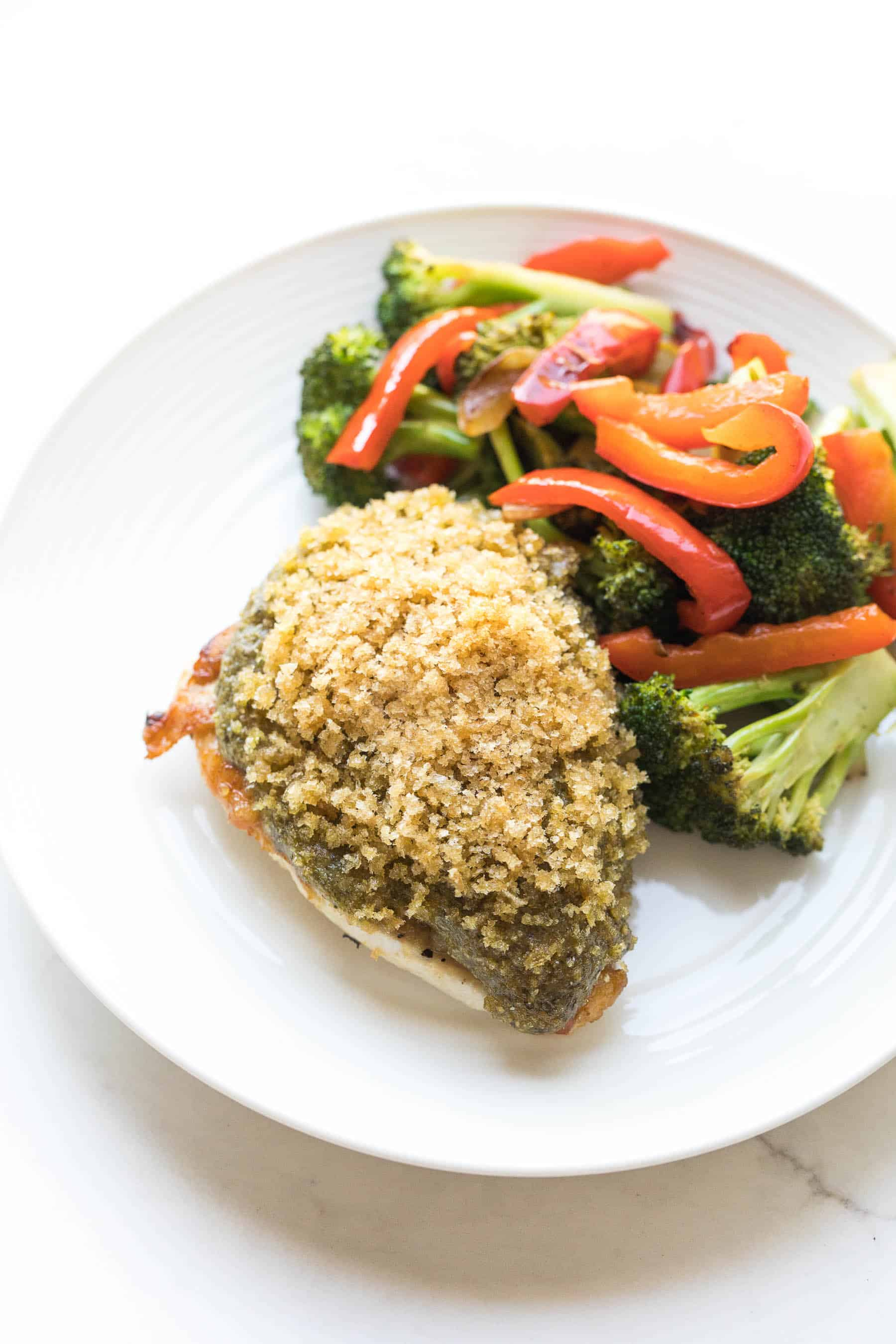 Crispy pesto chicken on a white plate with vegetables