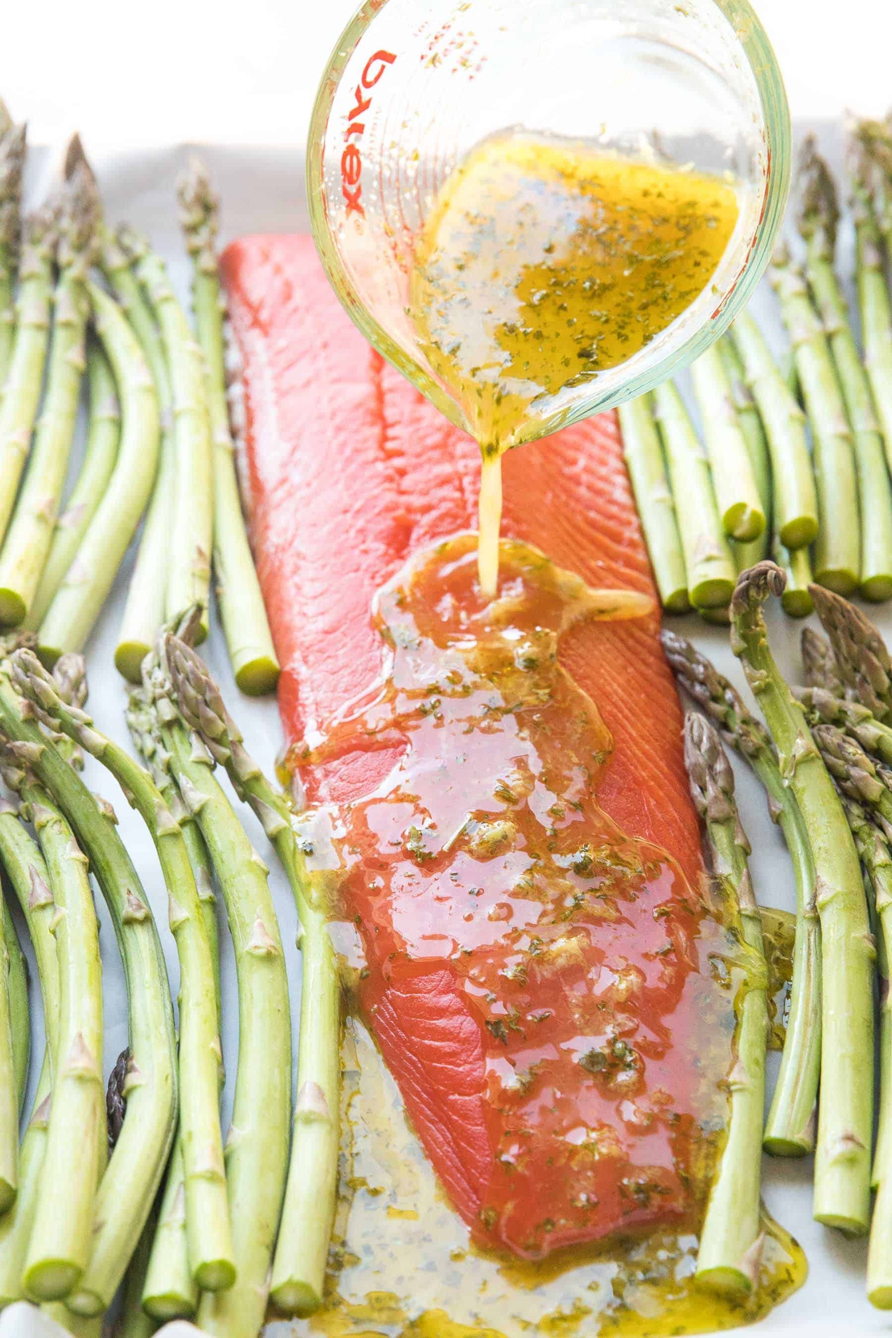 pouring marinade over sheet pan salmon and asparagus dinner
