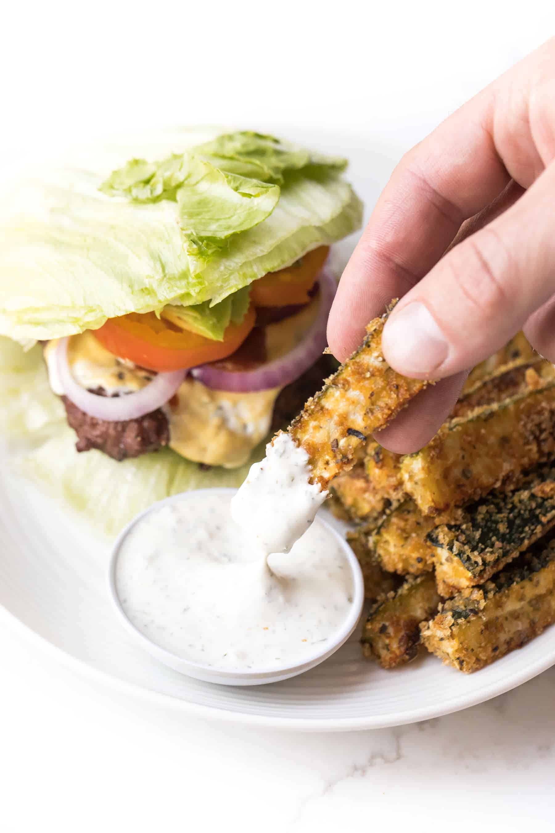 Hand dipping whole30 + keto zucchini fries in ranch dressing