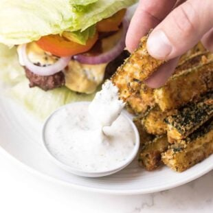 Hand dipping keto zucchini fries in ranch dressing on a white plate and white background with a lettuce wrapped burger on the plate