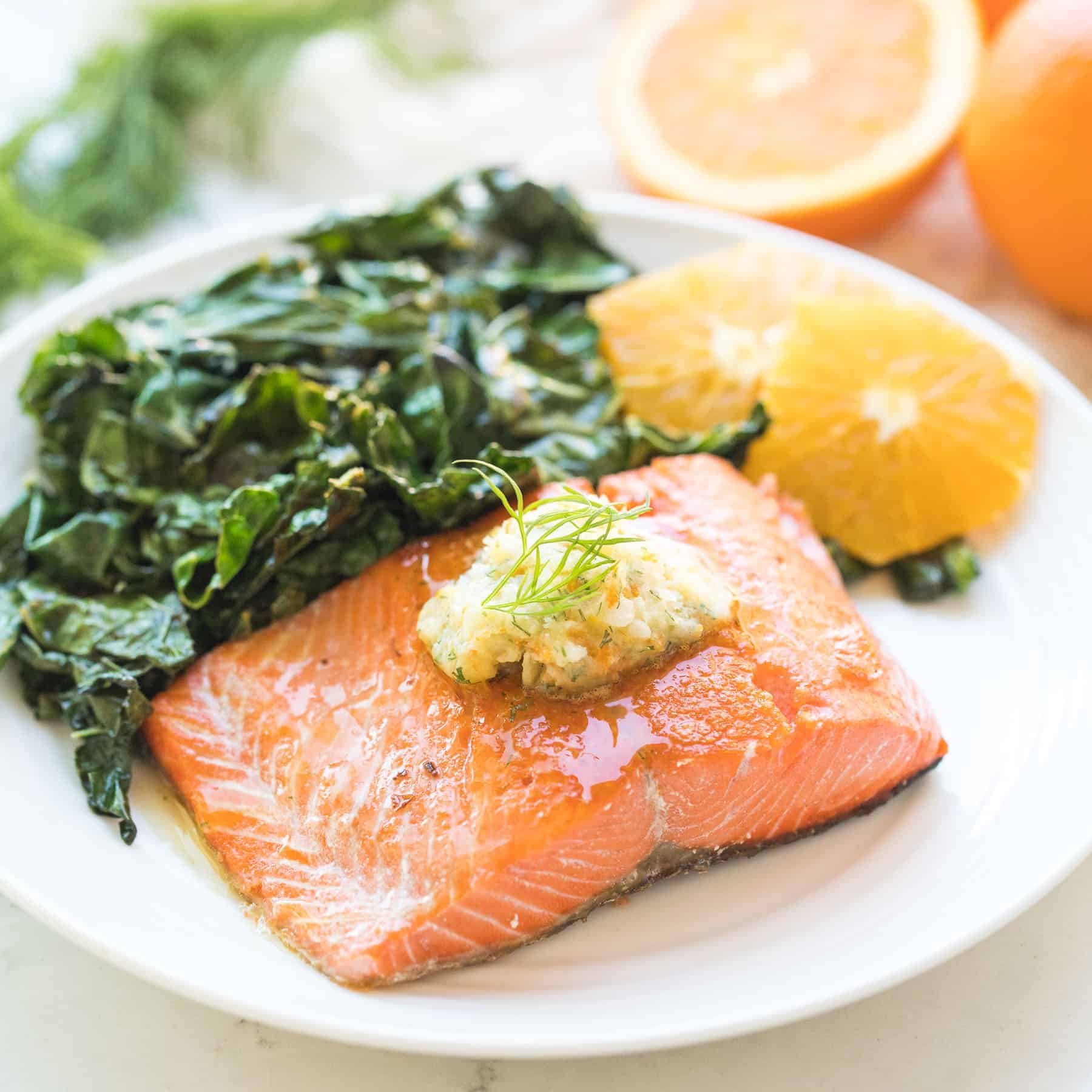 salmon on a white plate with butter on top next to peeled oranges and green kale salad