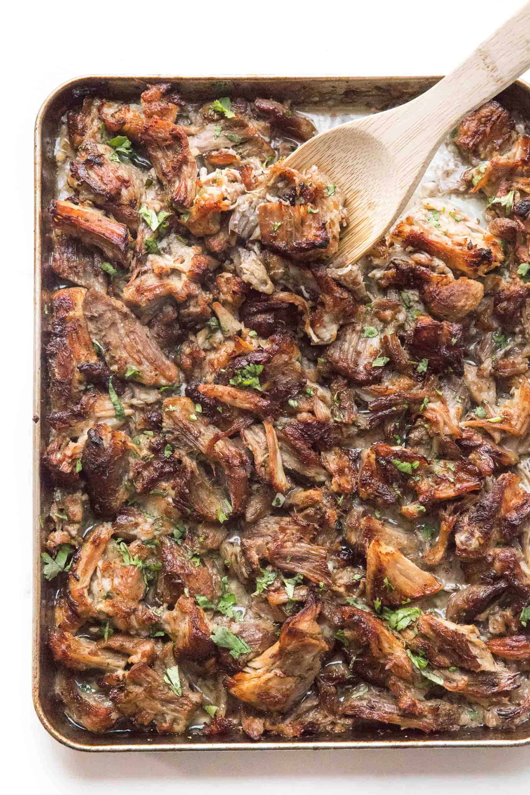 wooden spoon scooping crispy instant pot carnitas on a rimmed baking sheet sprinkled with cilantro