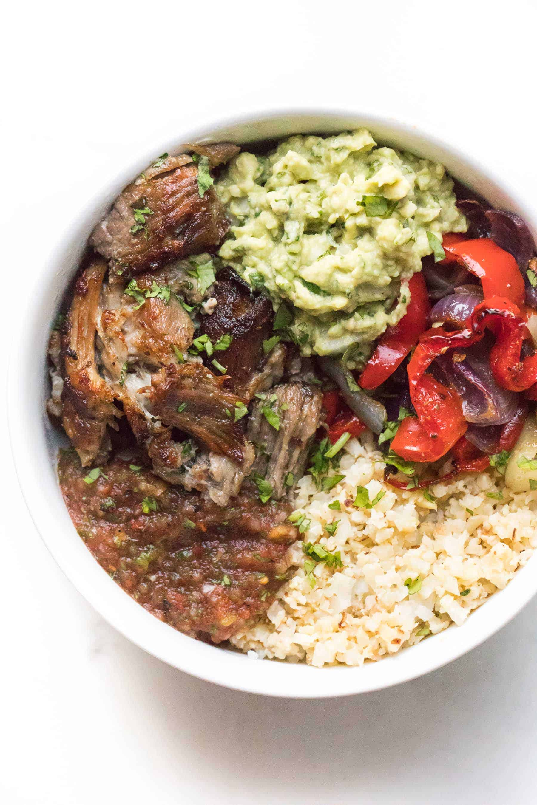 carnitas burrito bowl in a white plate on a white background
