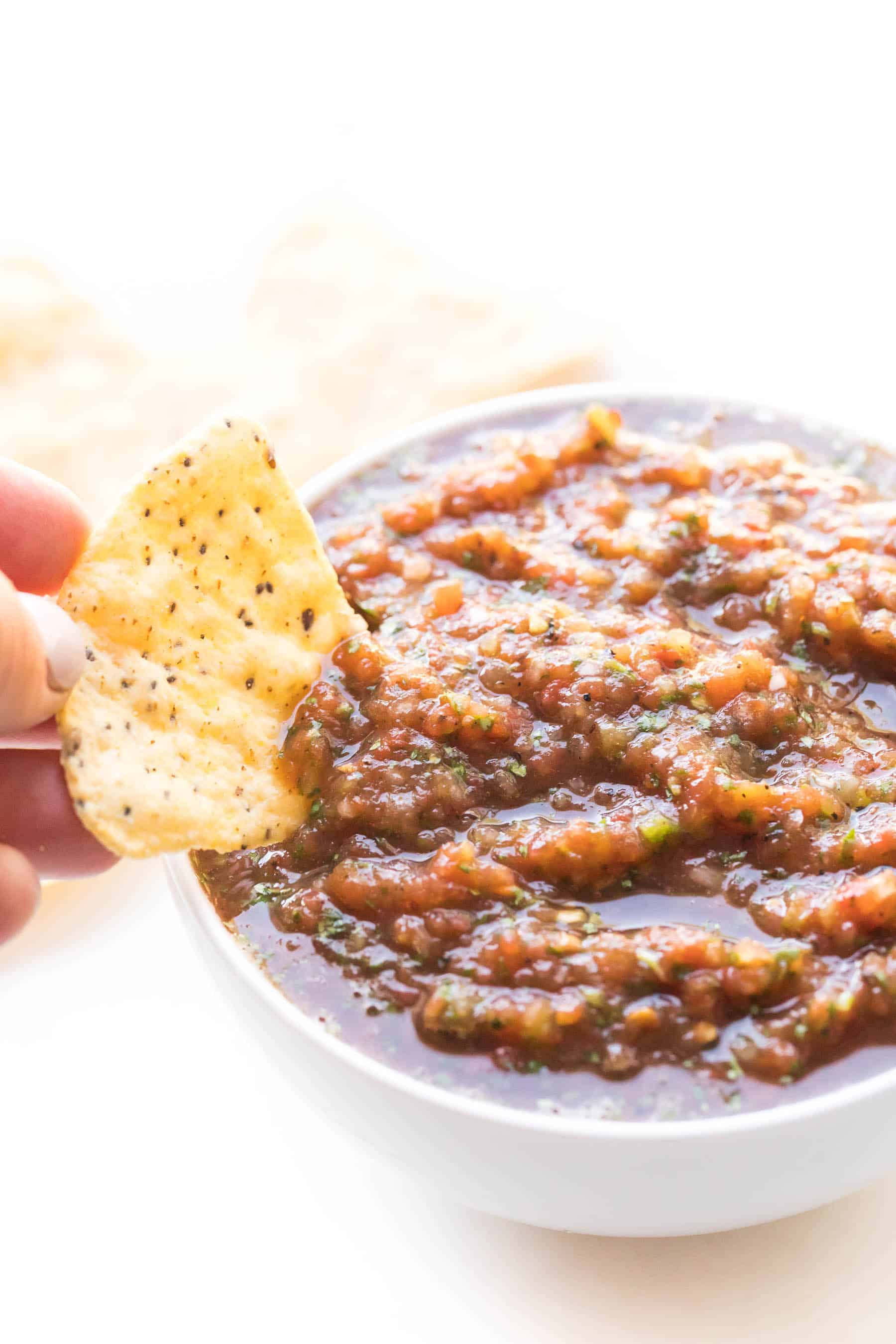 hand dipping a chip in homemade red salsa in a white bowl on a white background