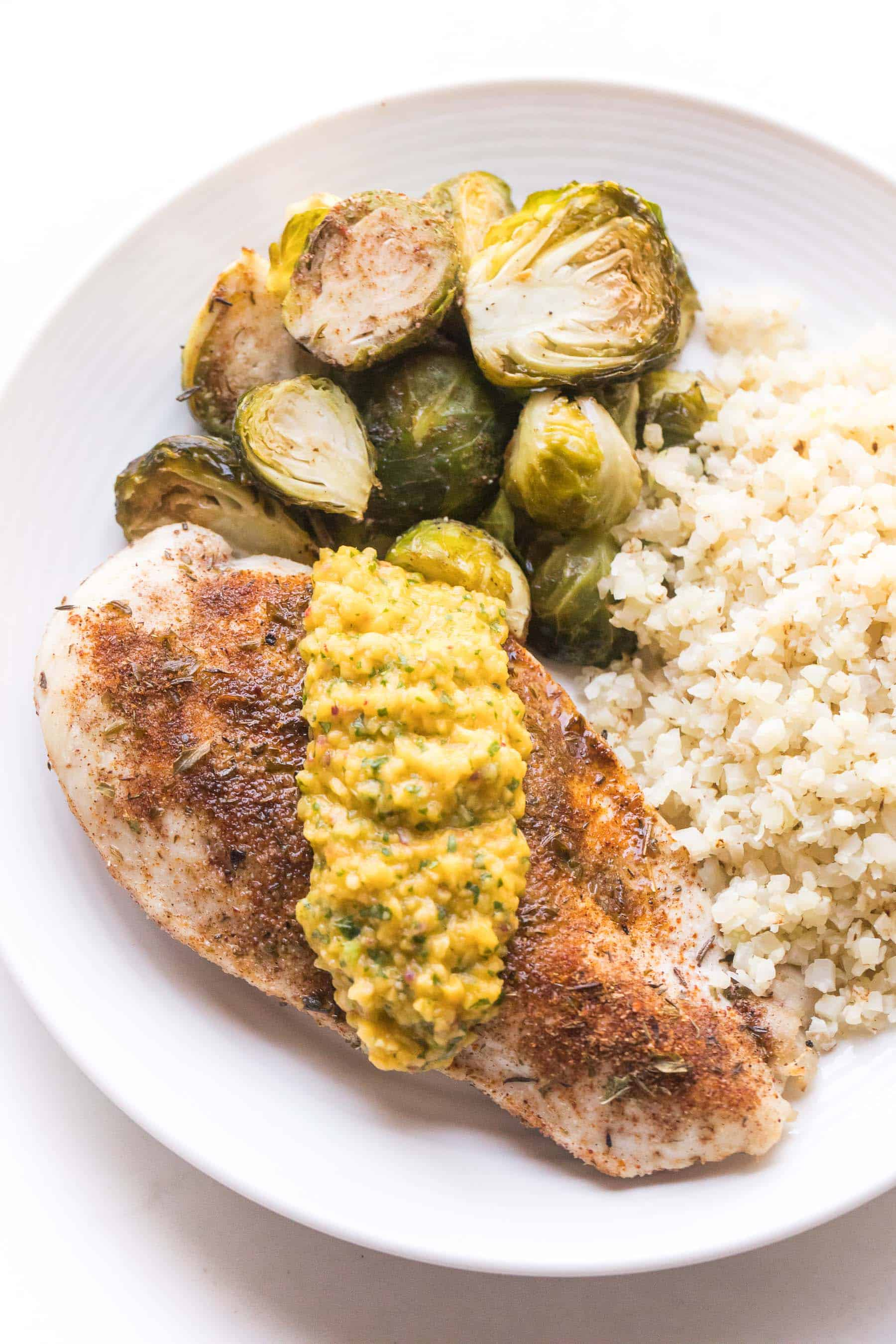 jamaican chicken topped with mango salsa with brussles sprouts and cauliflower rice on a white plate