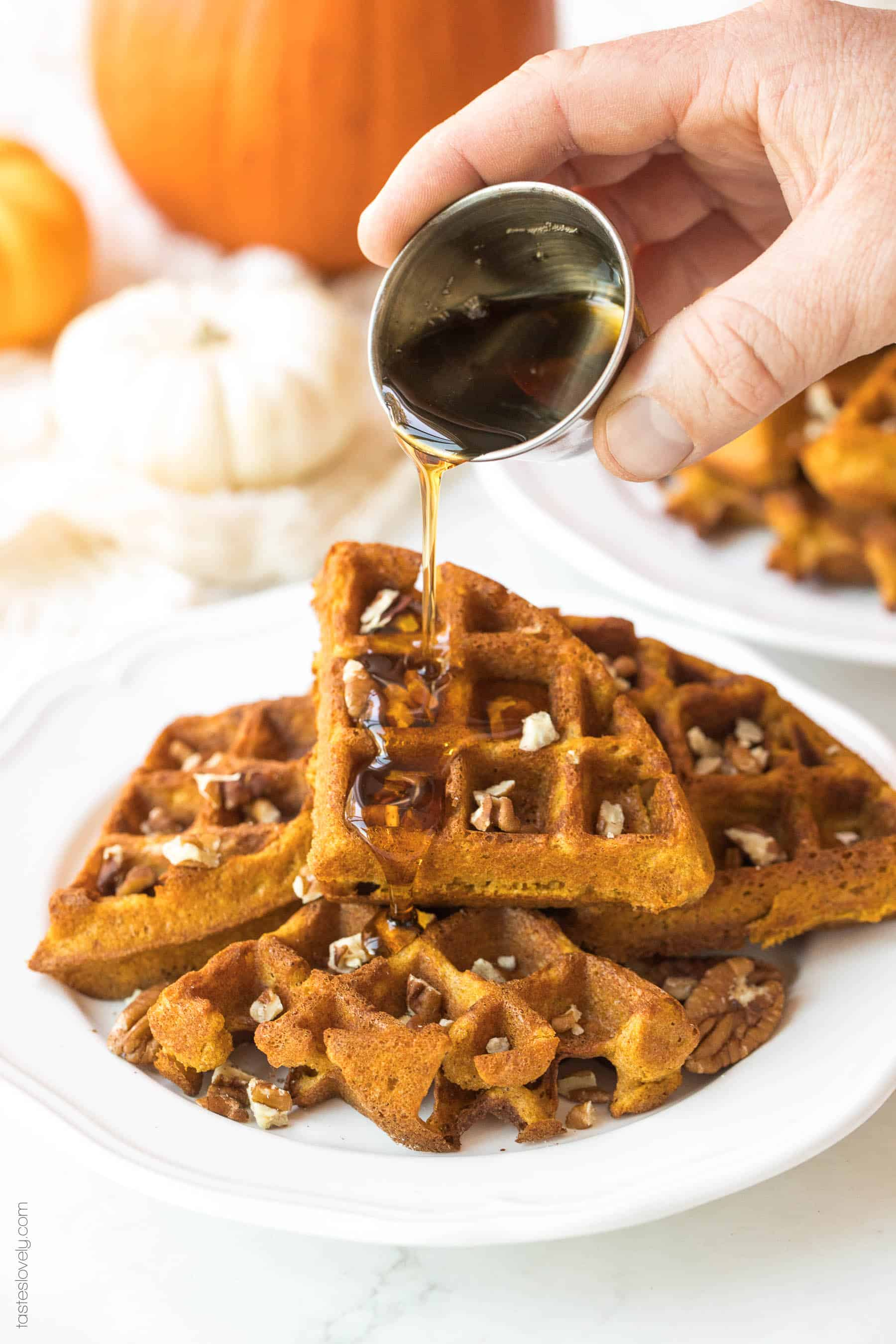 syrup being poured on top of pumpkin waffles