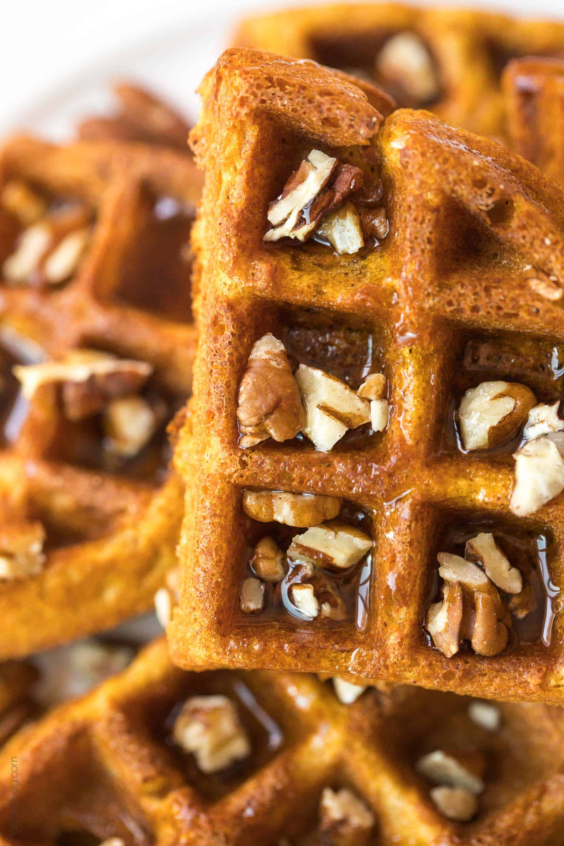 close up of pumpkin waffles with pecans and maple syrup