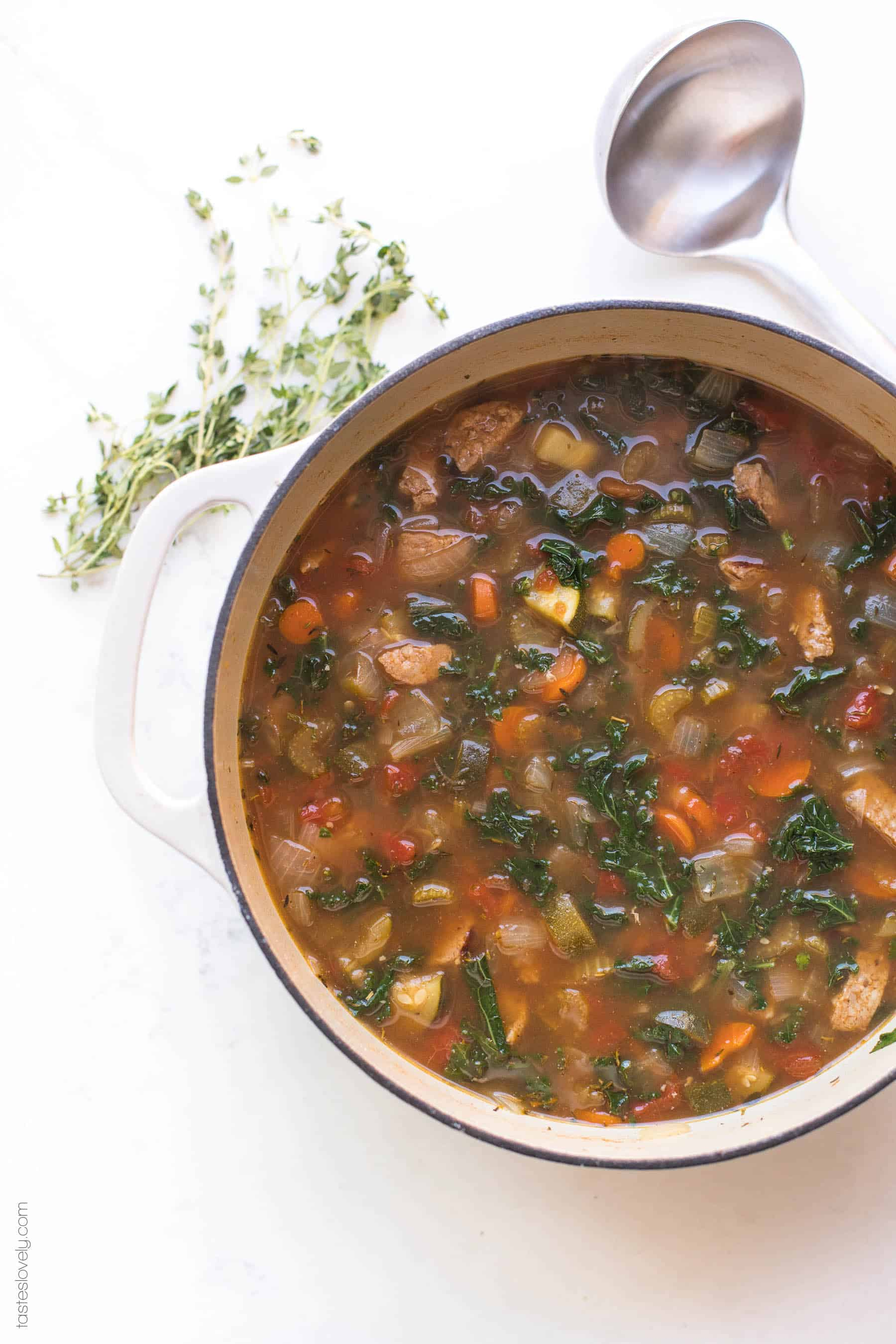 A dutch oven filled with sausage and kale vegetable soup