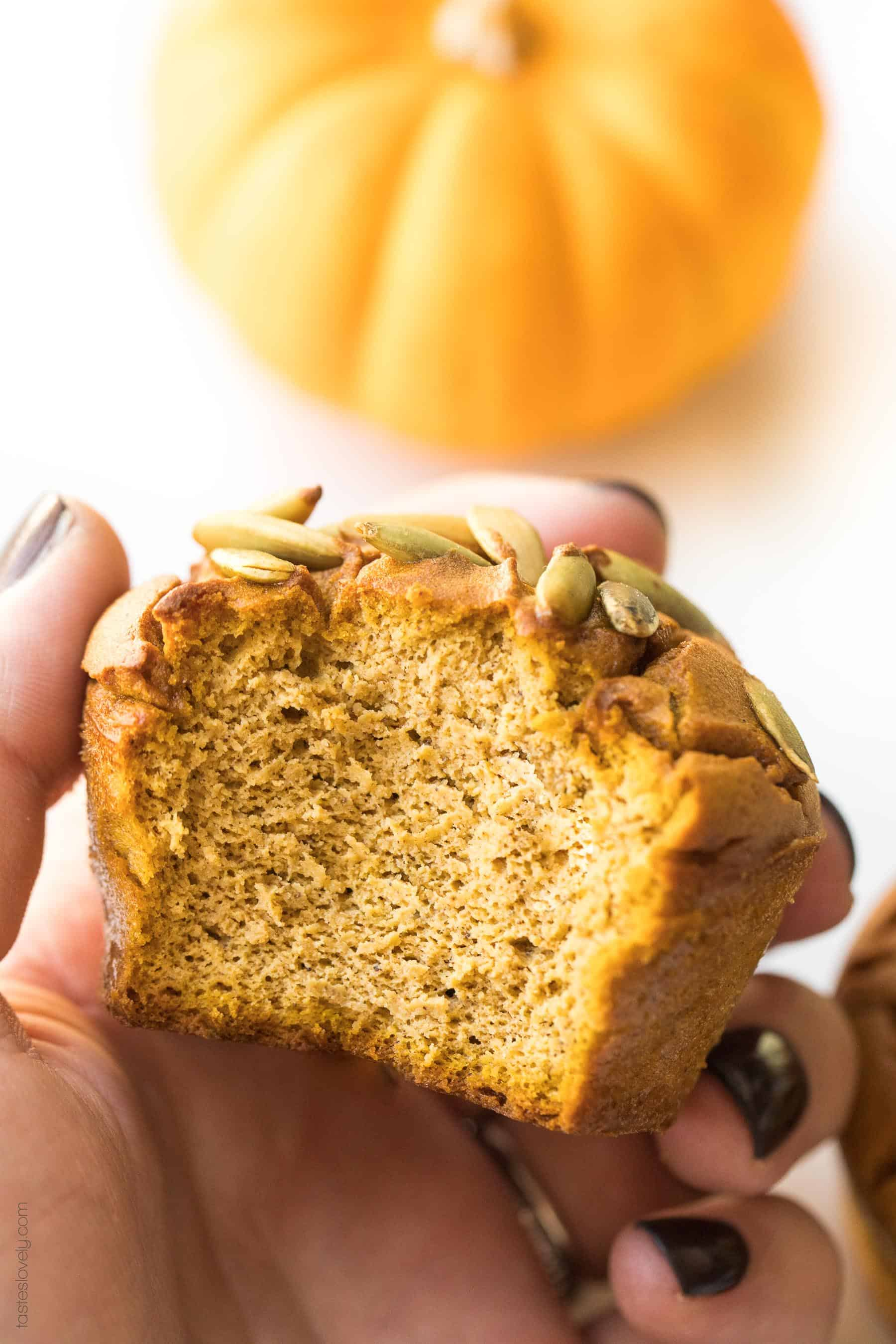a hand holding a paleo pumpkin muffin that has a bite taken out of it