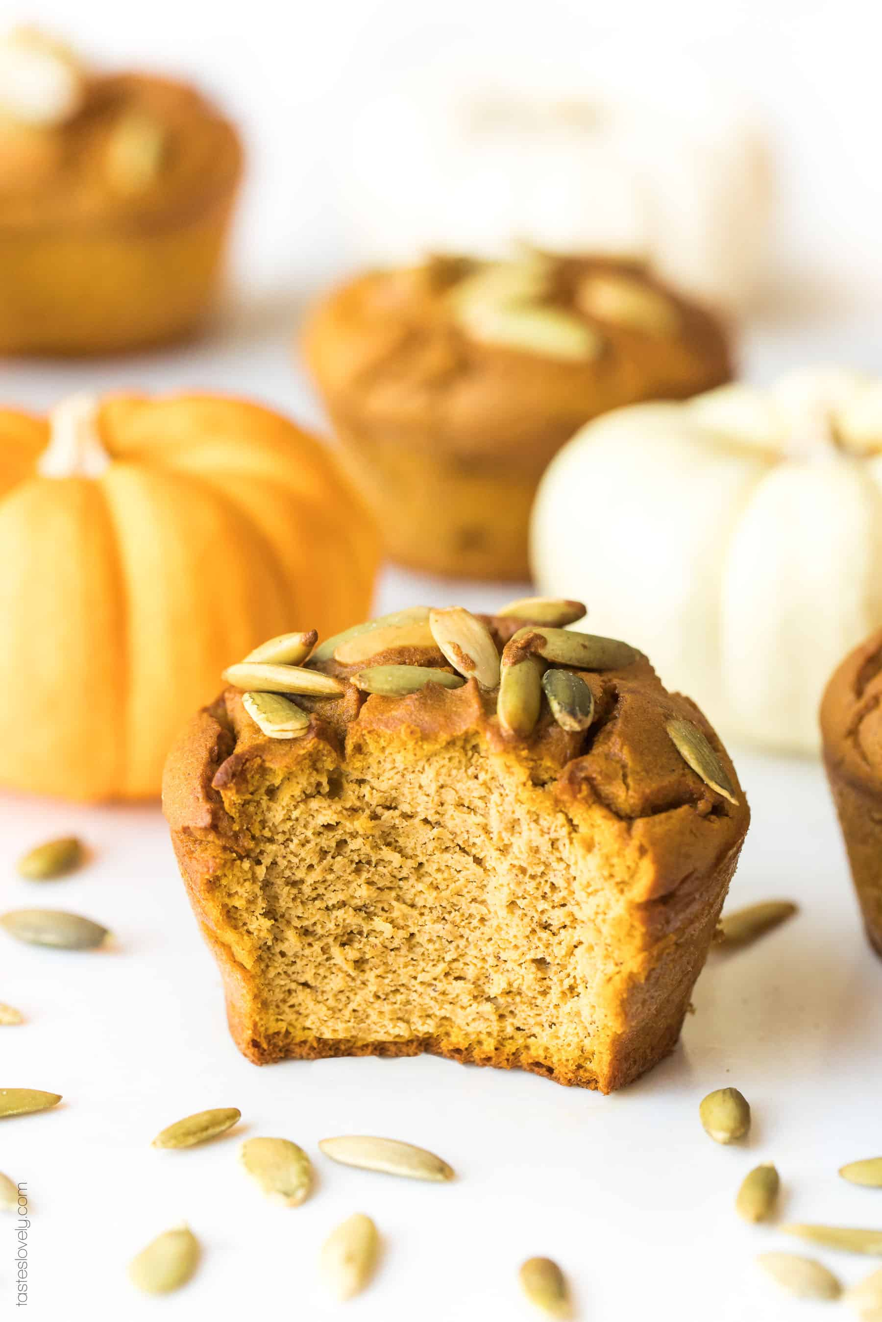 A paleo pumpkin muffin with a bite taken out of it with small pumpkins in the background