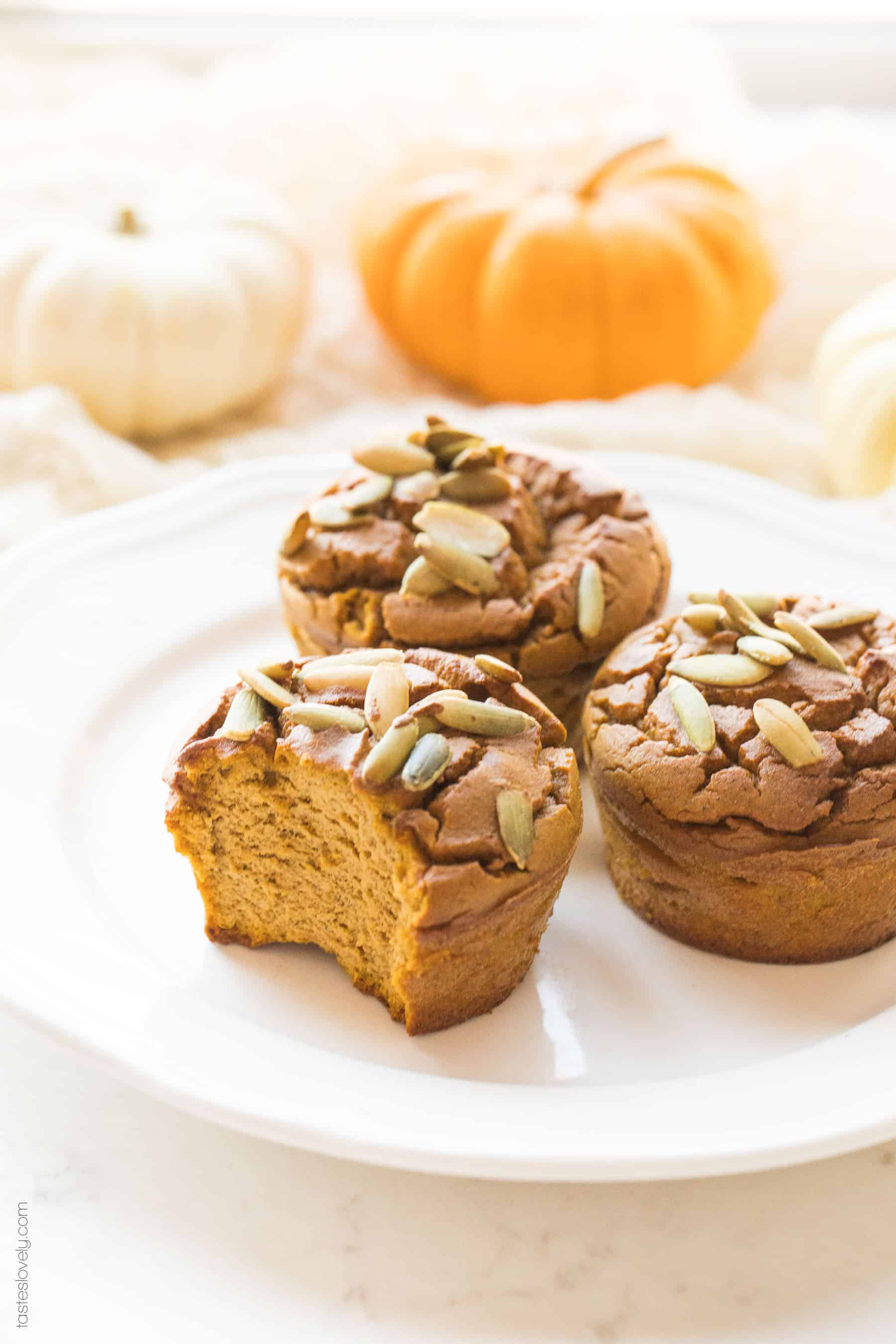 a plate of paleo pumpkin muffins, 1 has a bite taken out of it