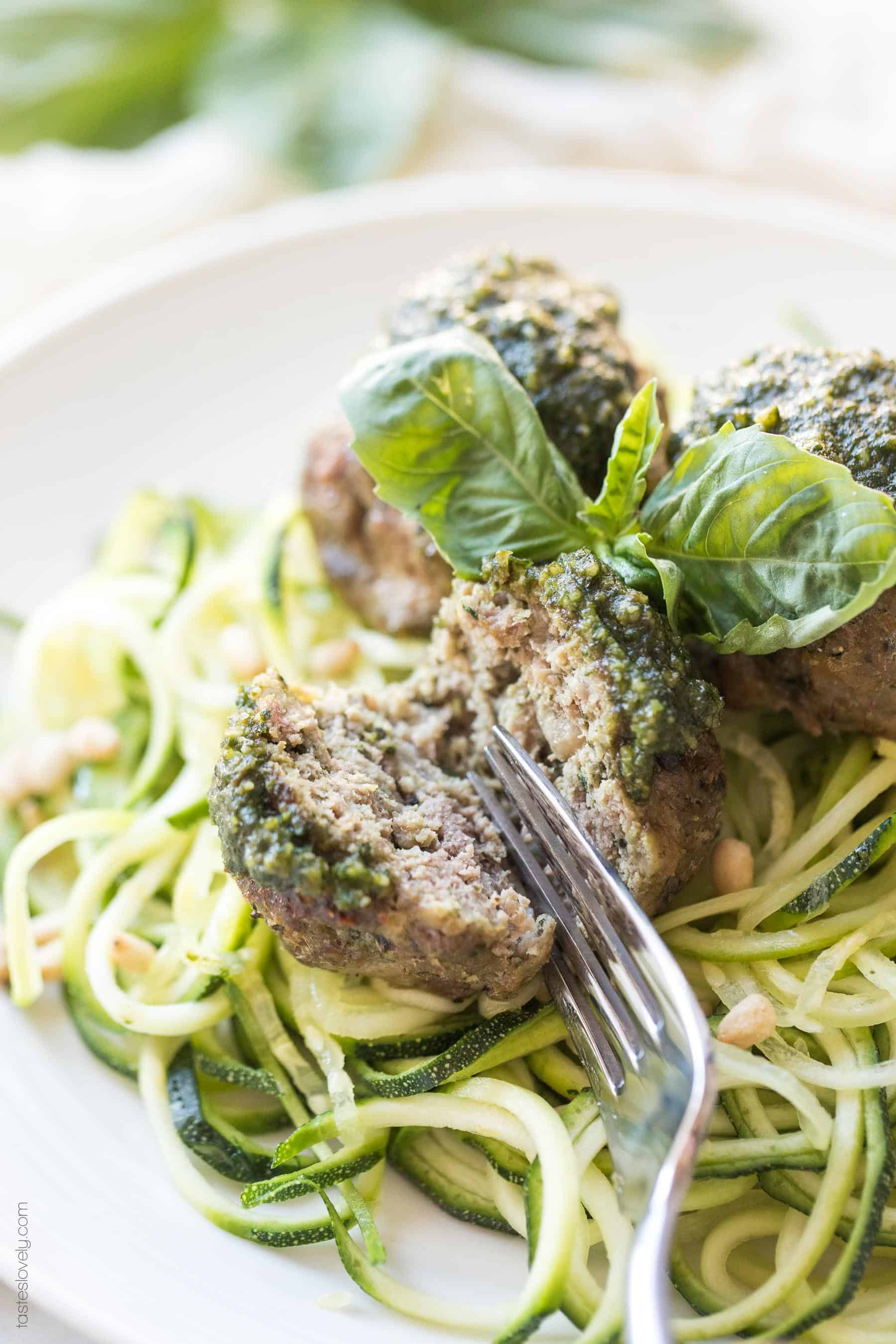 A fork cutting in to a pesto meatball on top of zucchini noodles
