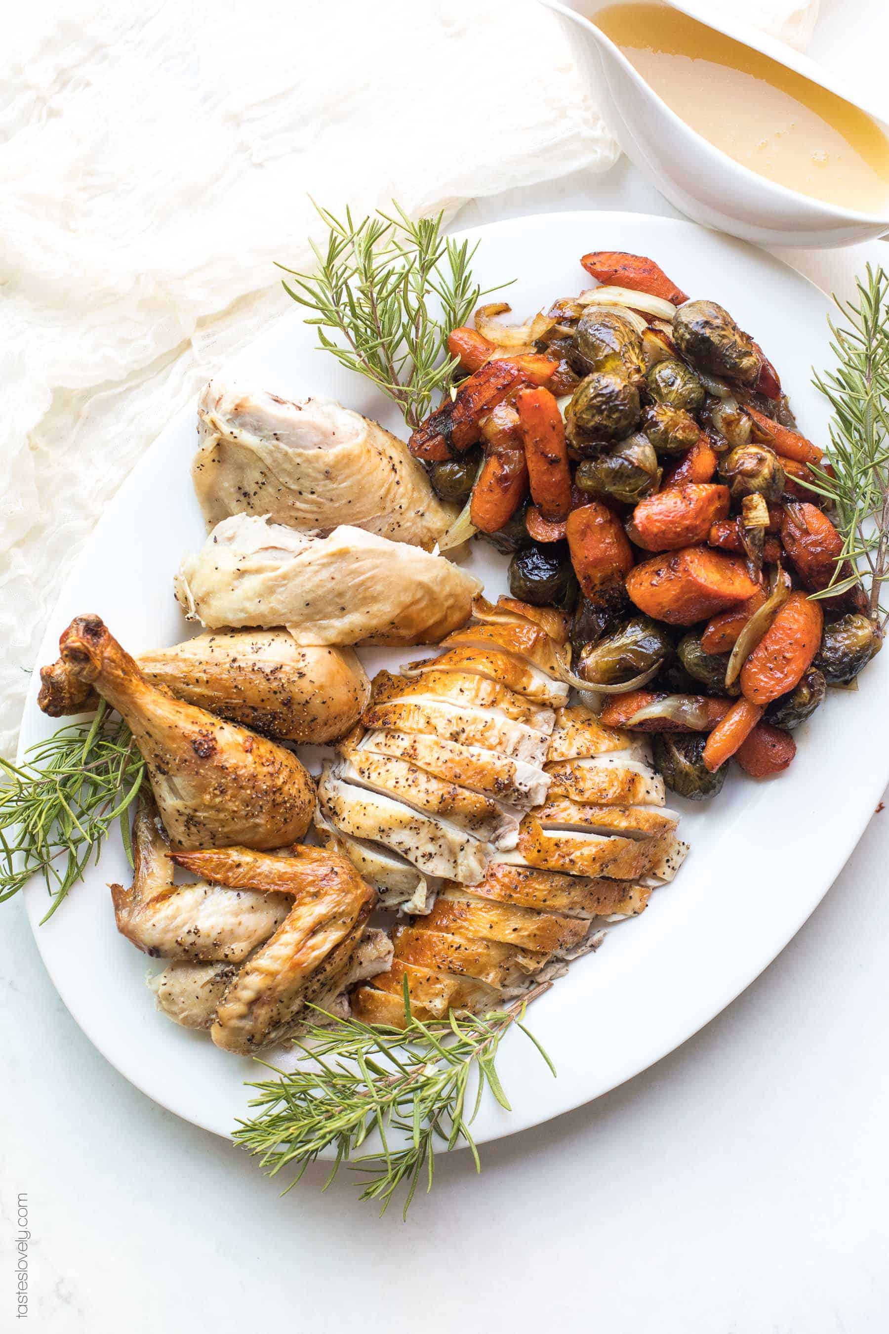 Cut up roast chicken on a platter with roasted root vegetables and sprigs of rosemary herbs