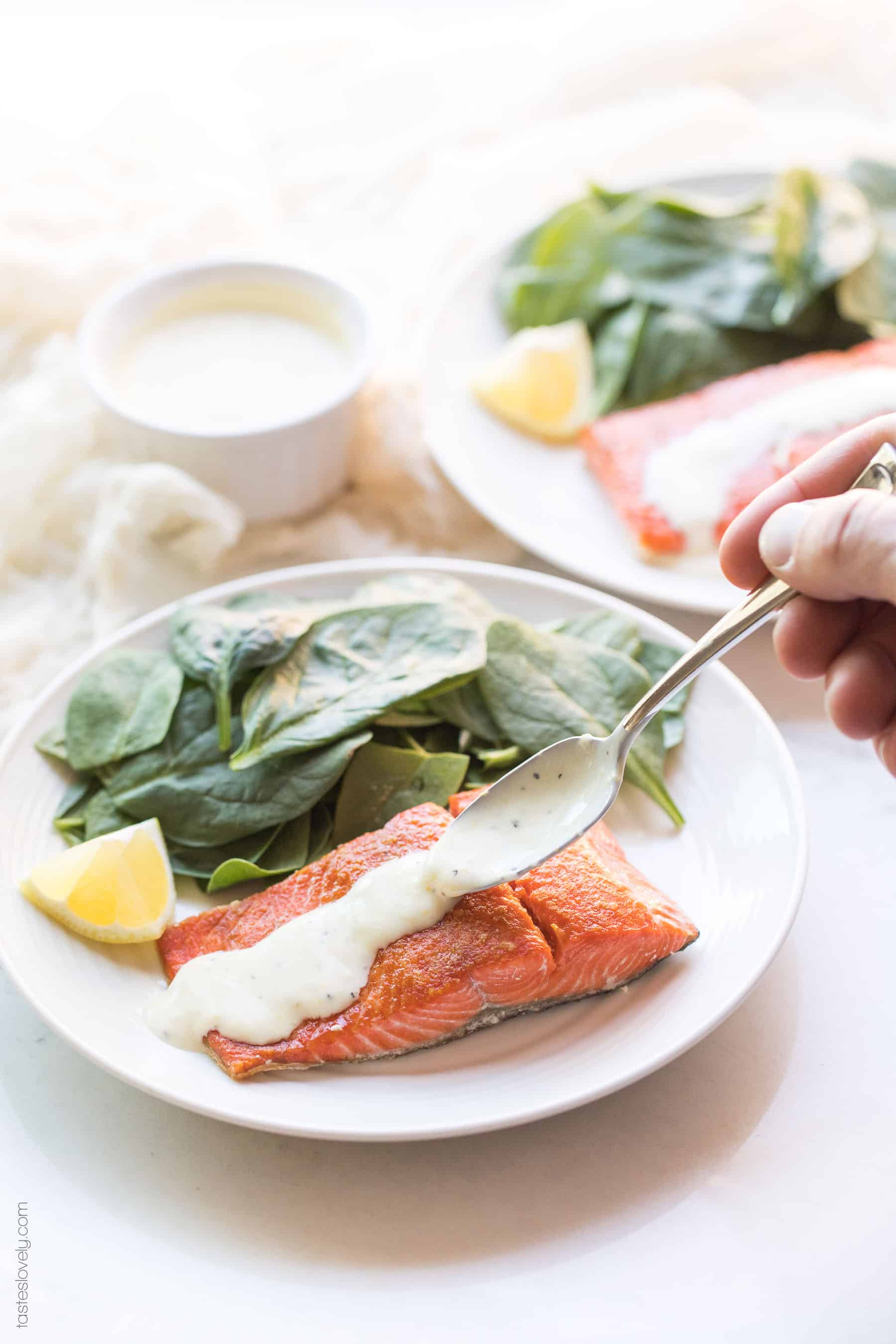 Pouring lemon garlic aioli over salmon on a plate with spinach