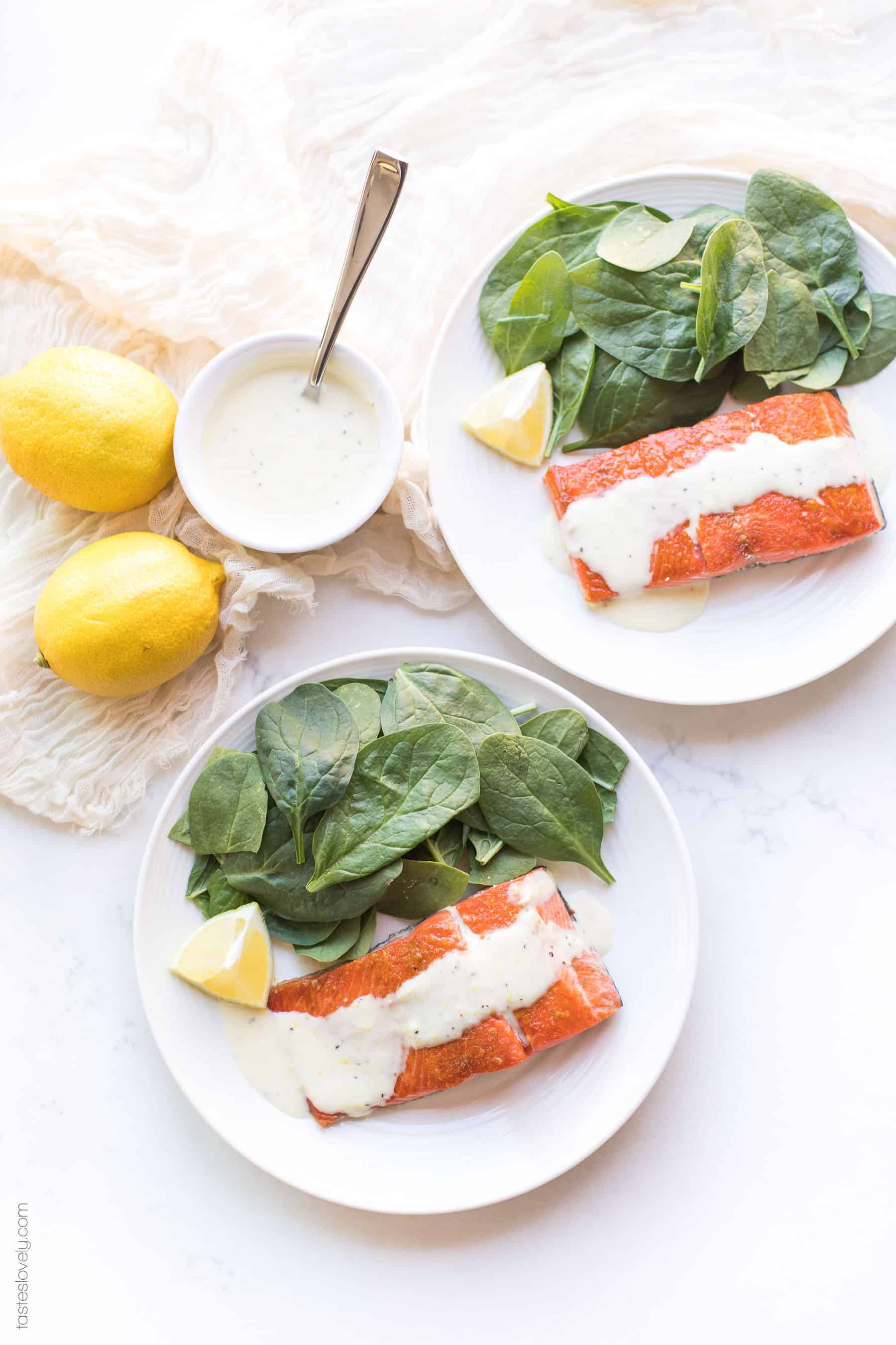 Salmon topped with a white sauce lemon garlic aioli on a plate with spinach