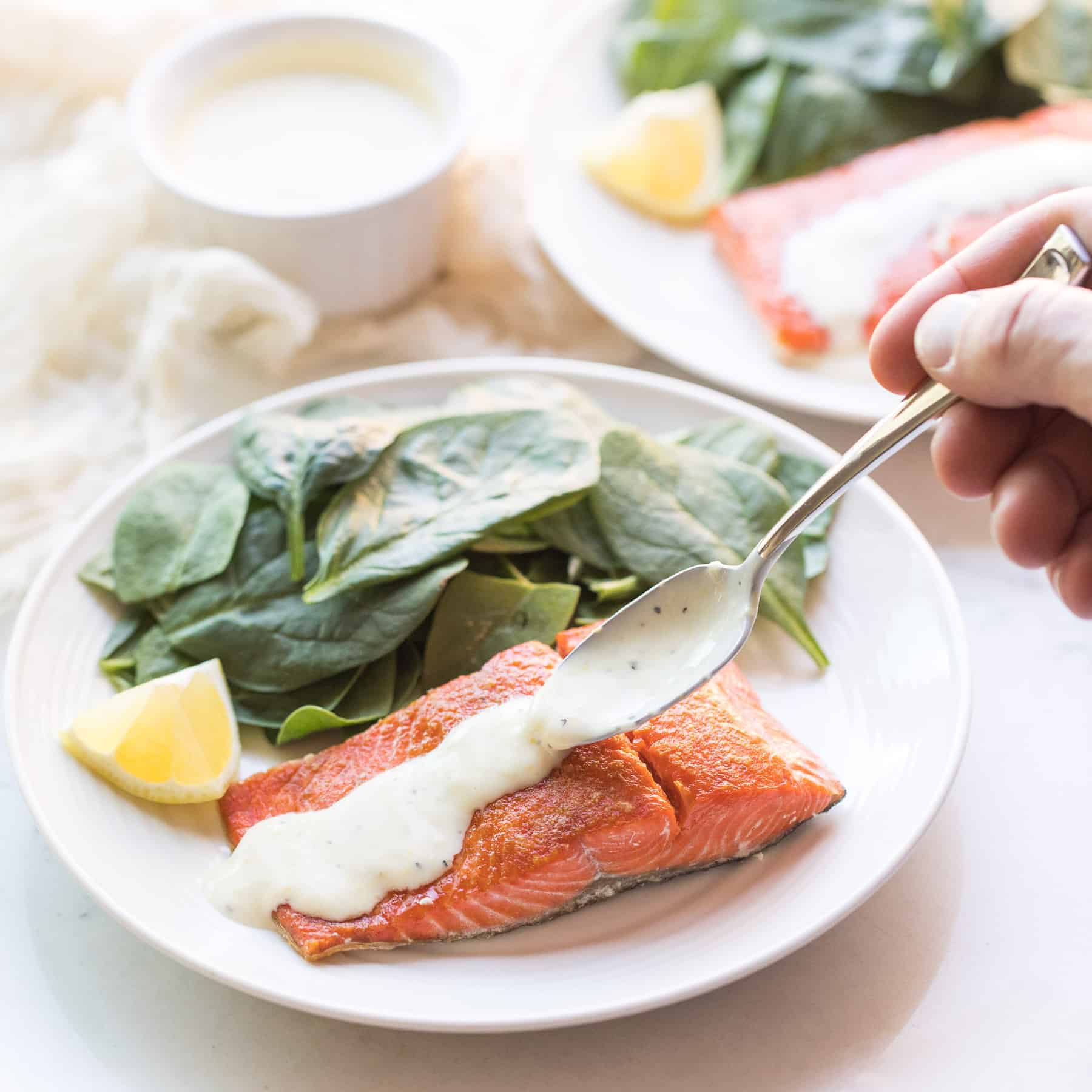 spinach and salmon on a white plate with a spoon drizzling sauce